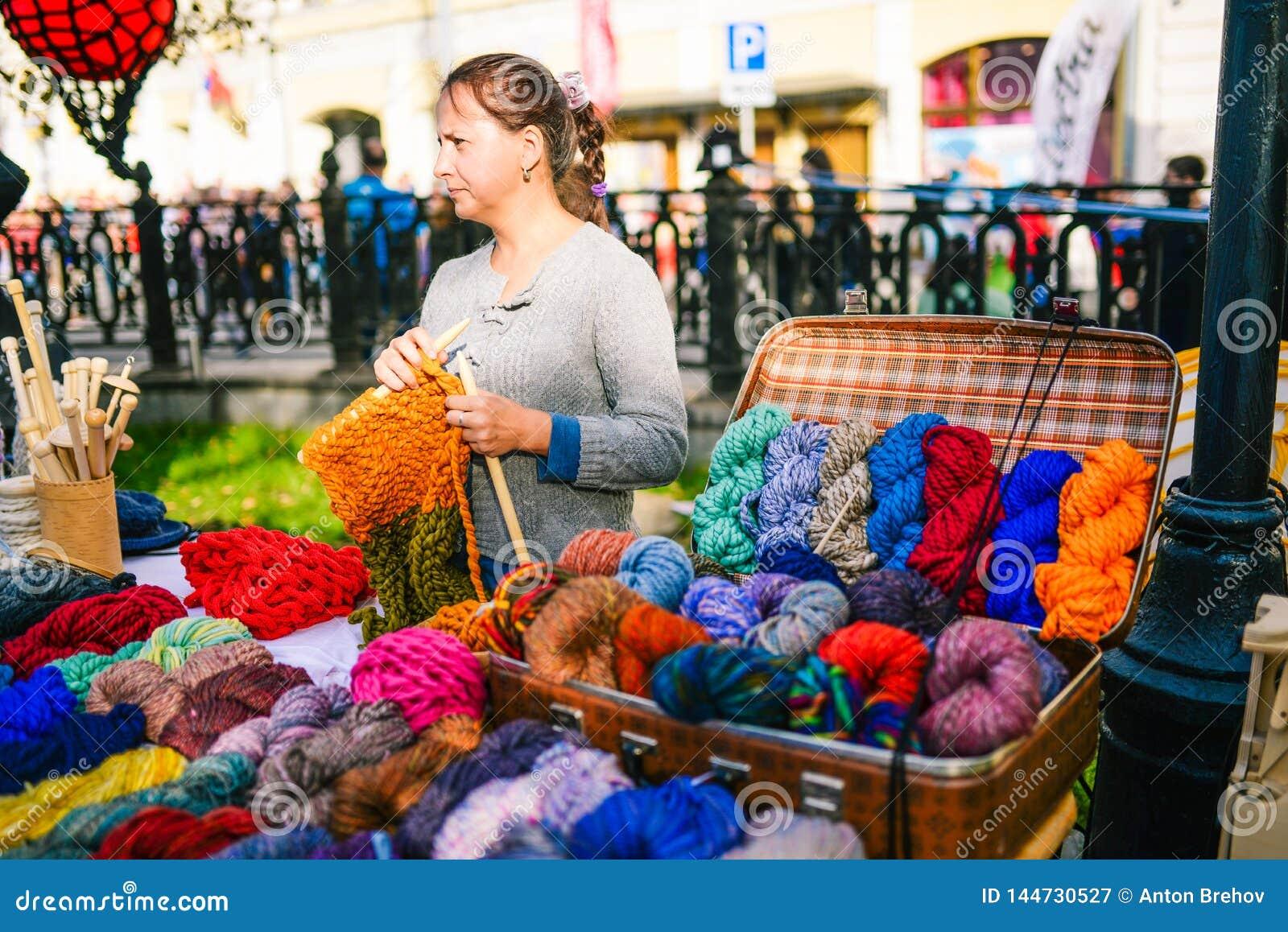 Rusia, ciudad Moscú - 6 de septiembre de 2014: Puntos de la mujer en la calle Las manos de las mujeres hacen punto un producto c
