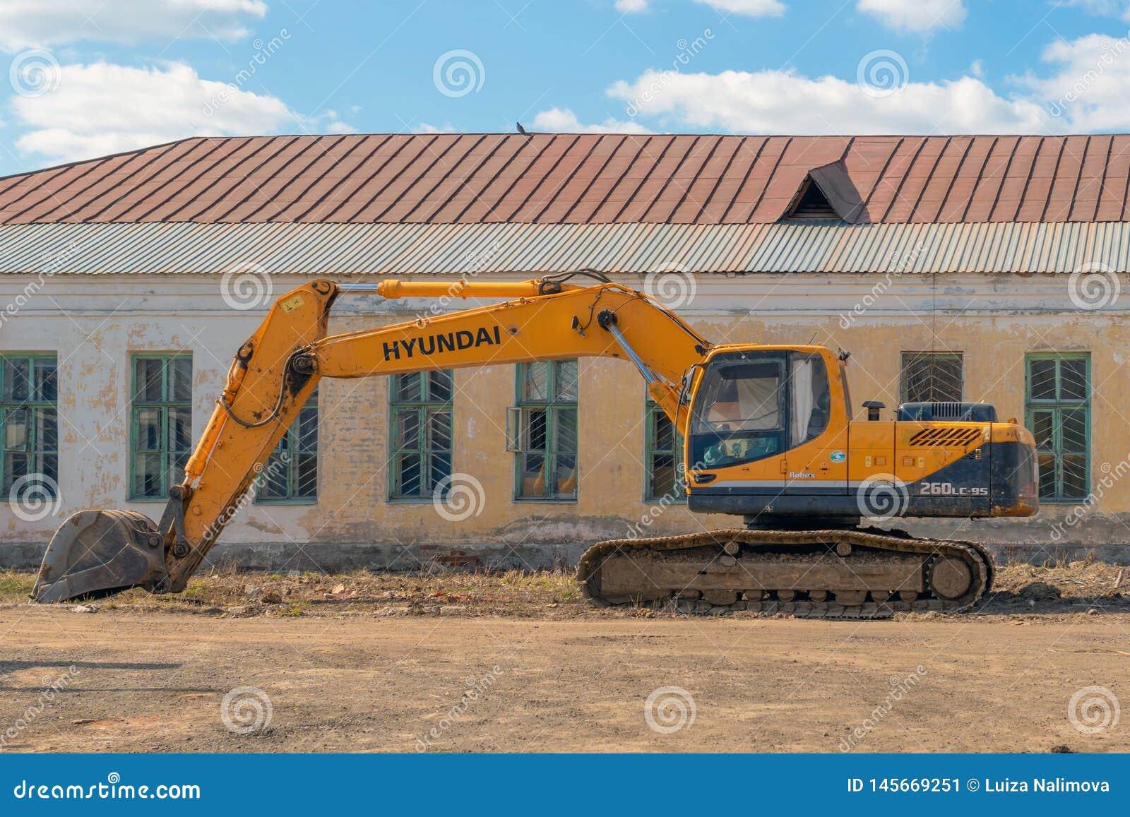 Rusia, Kaz?n - 20 de abril de 2019: Excavador amarillo en el fondo de un edificio abandonado