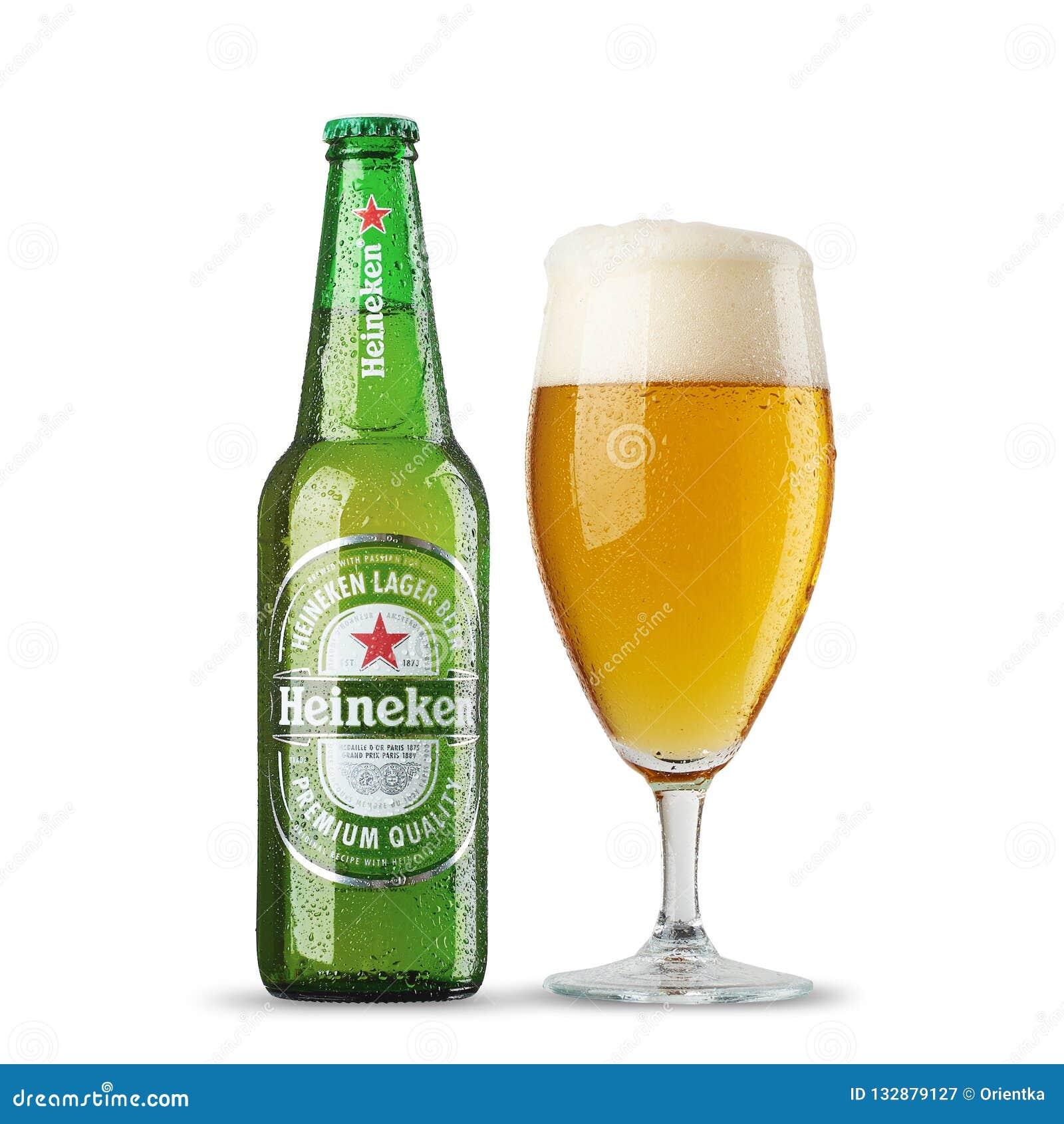 RUSIA, StPetersburg, el 9 de julio de 2017 ottle de Heineken Lager Beer con el vidrio en el fondo blanco