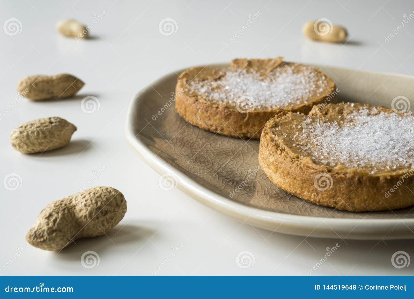 Rusk z Holenderskim masłem orzechowym i cukierem, na bielu stole