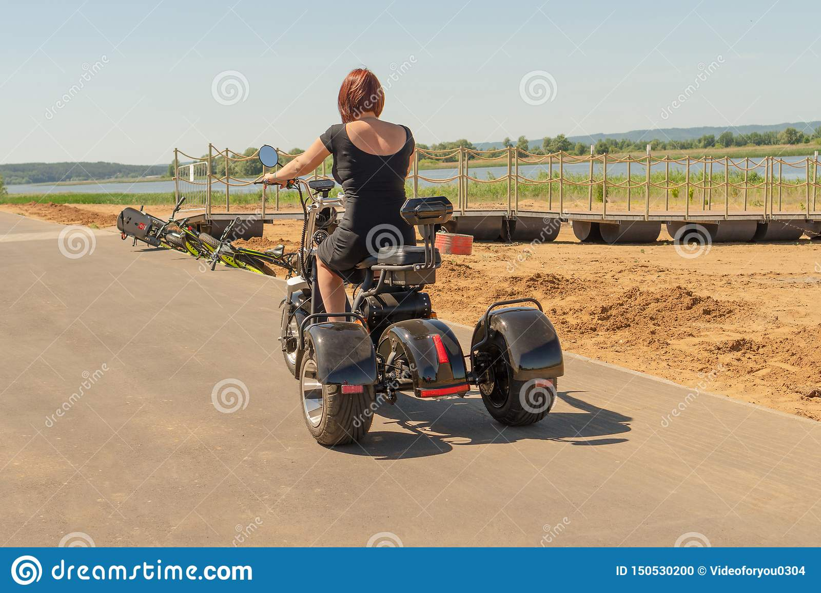 Rusland, Bolgar - Juni 08, 2019 Kol Gali Resort Spa: Een jong meisje in een zwarte kleding met rood haar die haar three-wheeled e