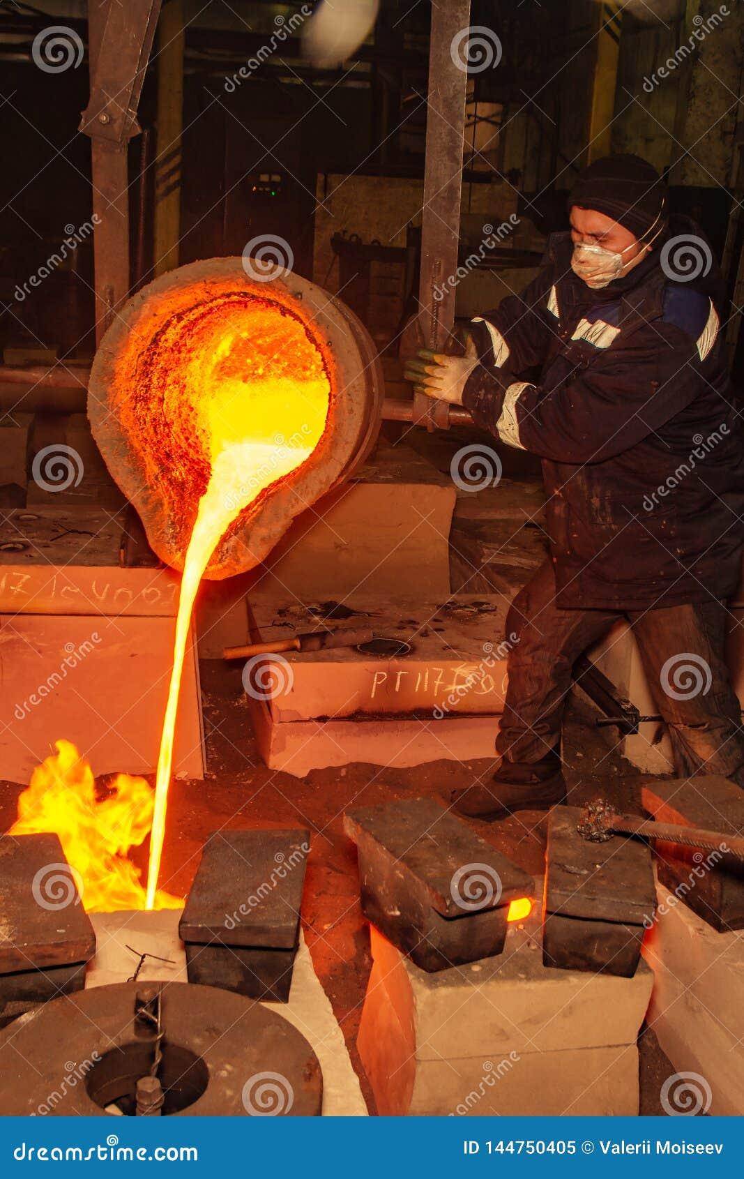 Rusland, Ryazan 14 Februari 2019 - de arbeider giet resten van gesmolten metaal in fabriek van metaal het gieten proces