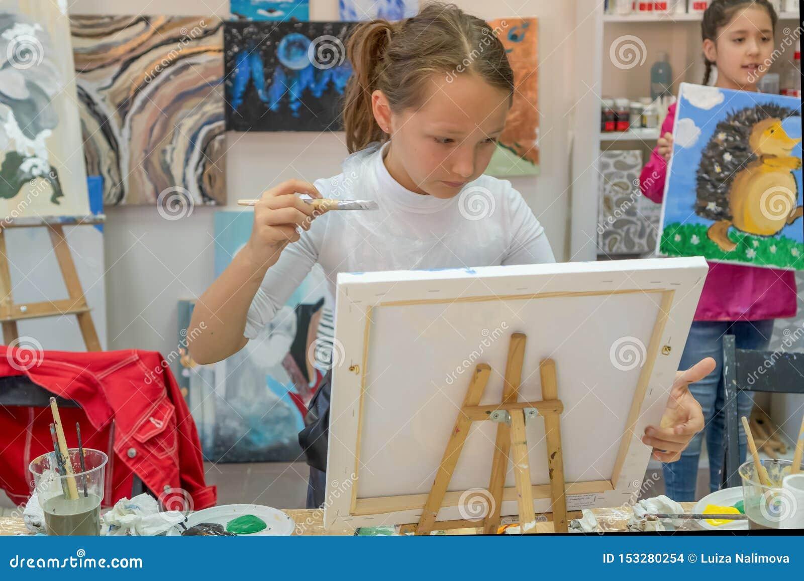 Rusland, Tatarstan, 21 April, 2019 Mooi meisje met in hand borstel Creatief tienermeisje die een beeld op schildersezel paitning