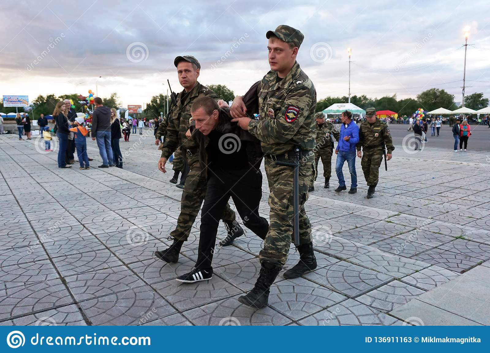 Russia, city of Magnitogorsk, - August, 7, 2015. Russian police escort the alleged offender to the exit from the town square. Law