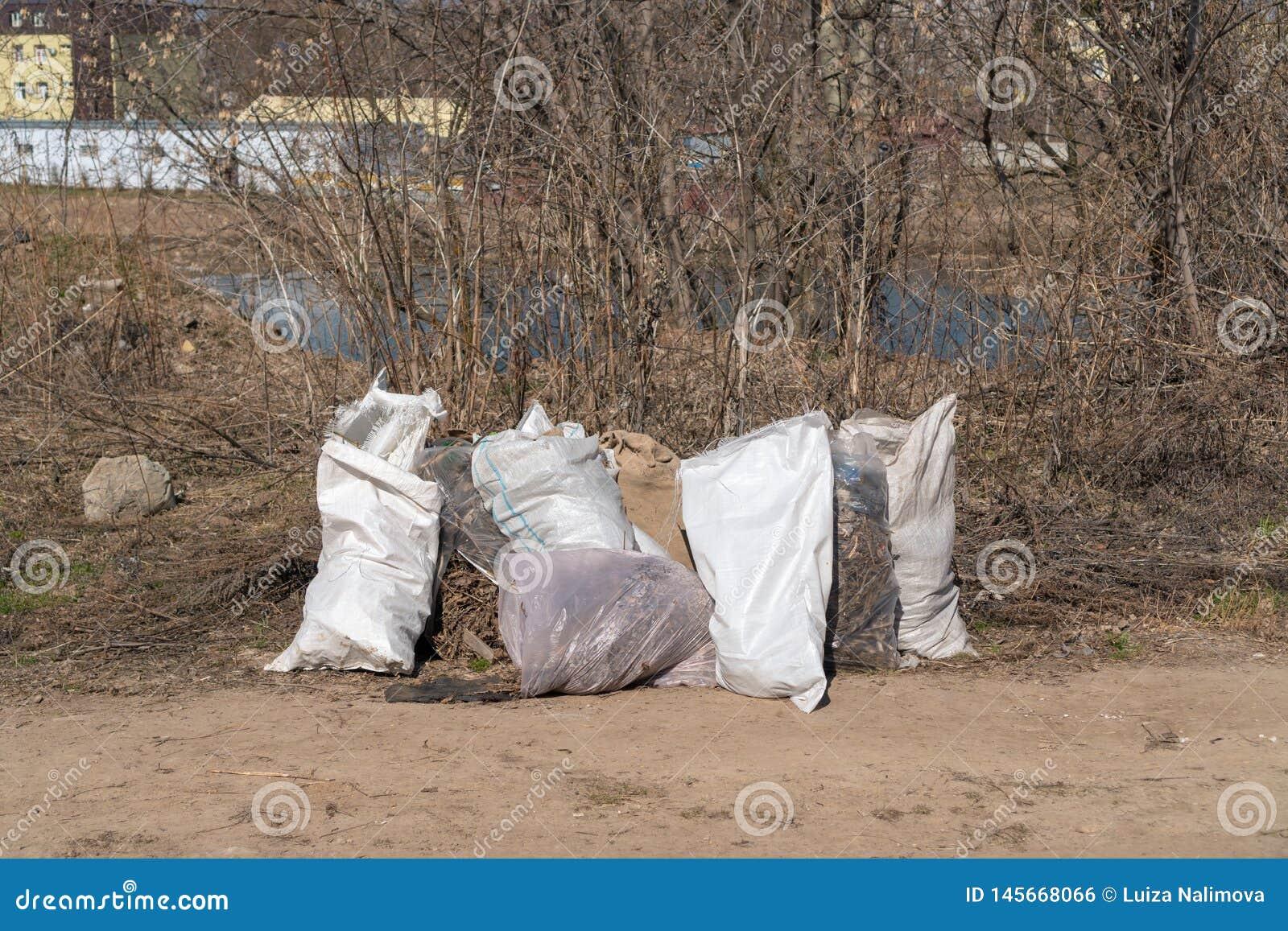 Russia, Kazan - April 20, 2019: Garbage bags on the river bank.