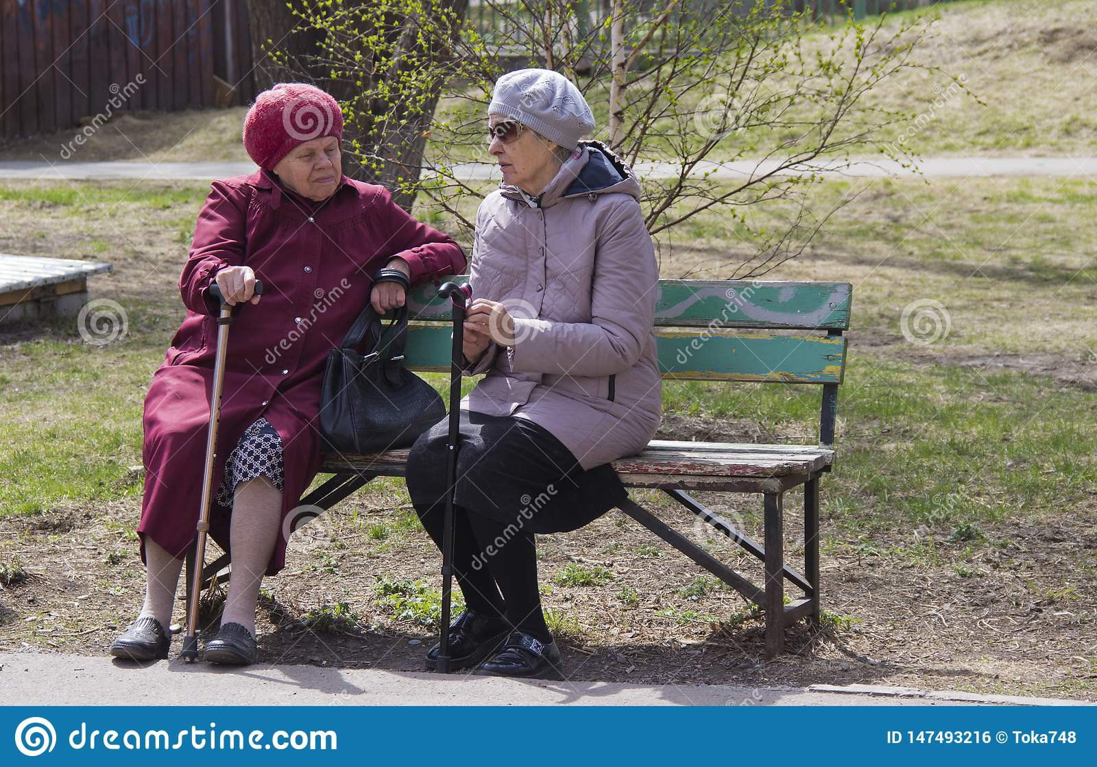 Women of retirement age sit on a bench and discuss the news