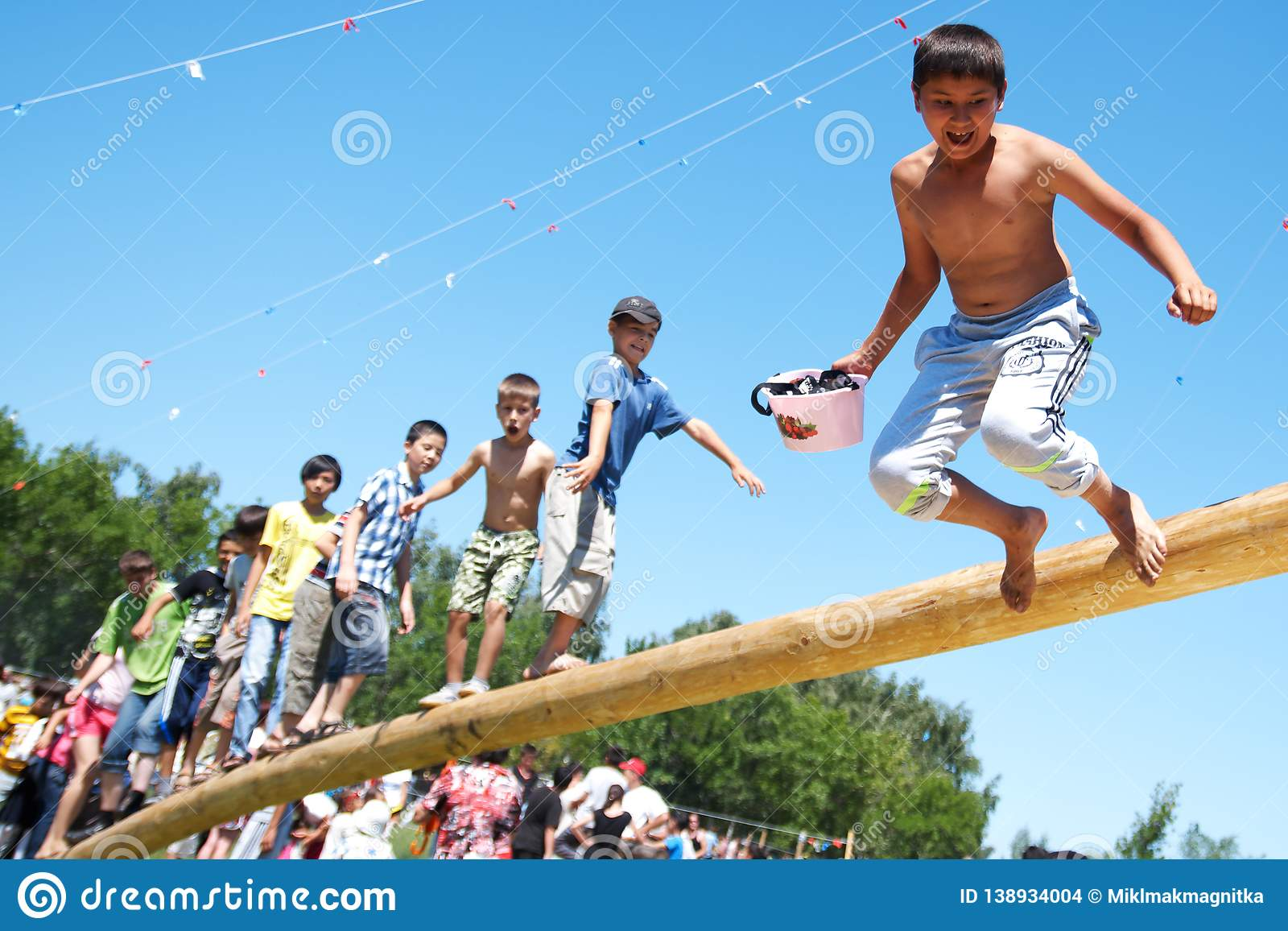 Russia, Magnitogorsk, - June, 16, 2011. Boys play national games, jump on a log, during Sabantuy - the national holiday of the