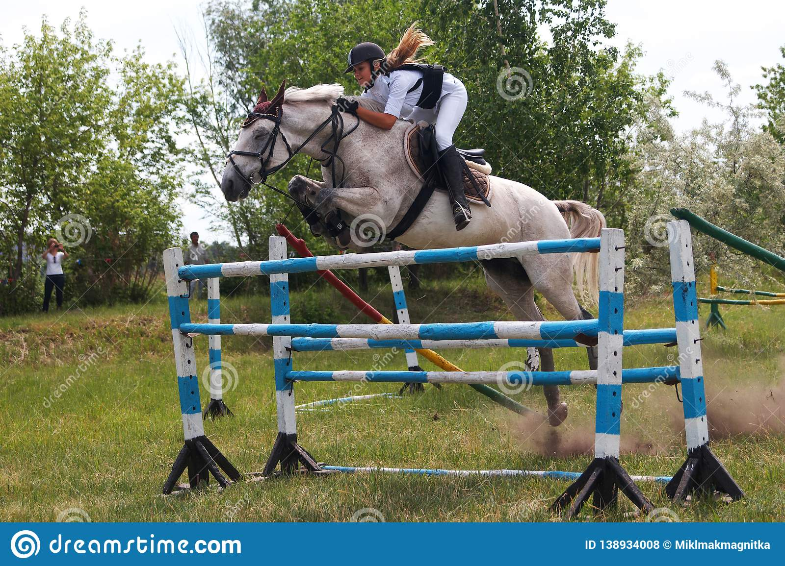 Russia, Magnitogorsk, - June, 14, 2014. A rider on a horse jumps over a high barrier during a performance at Sabantuy - the