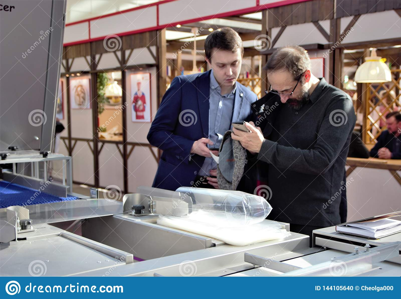 03.14.2019 Russia, Moscow. Exhibition Modern Bakery Moscow,  men remove on the camera mobile phone.