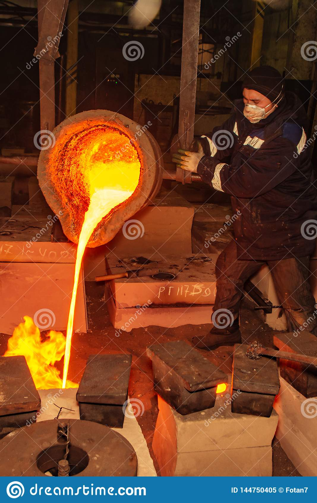 Russia, Ryazan 14 Feb 2019 - worker pours remnants of molten metal in factory of metal casting process