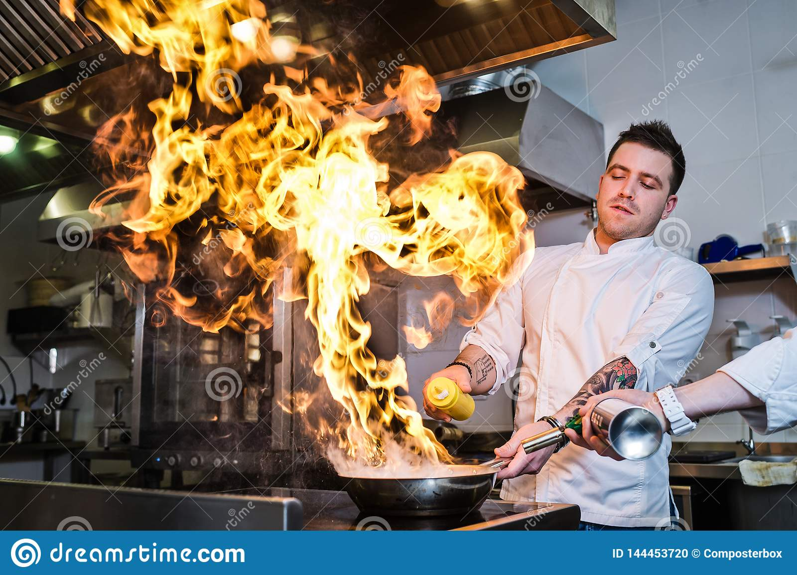 Russia, St. Petersburg, 03.17.2019 - chef is making flambe in a restaurant kitchen, dark background.