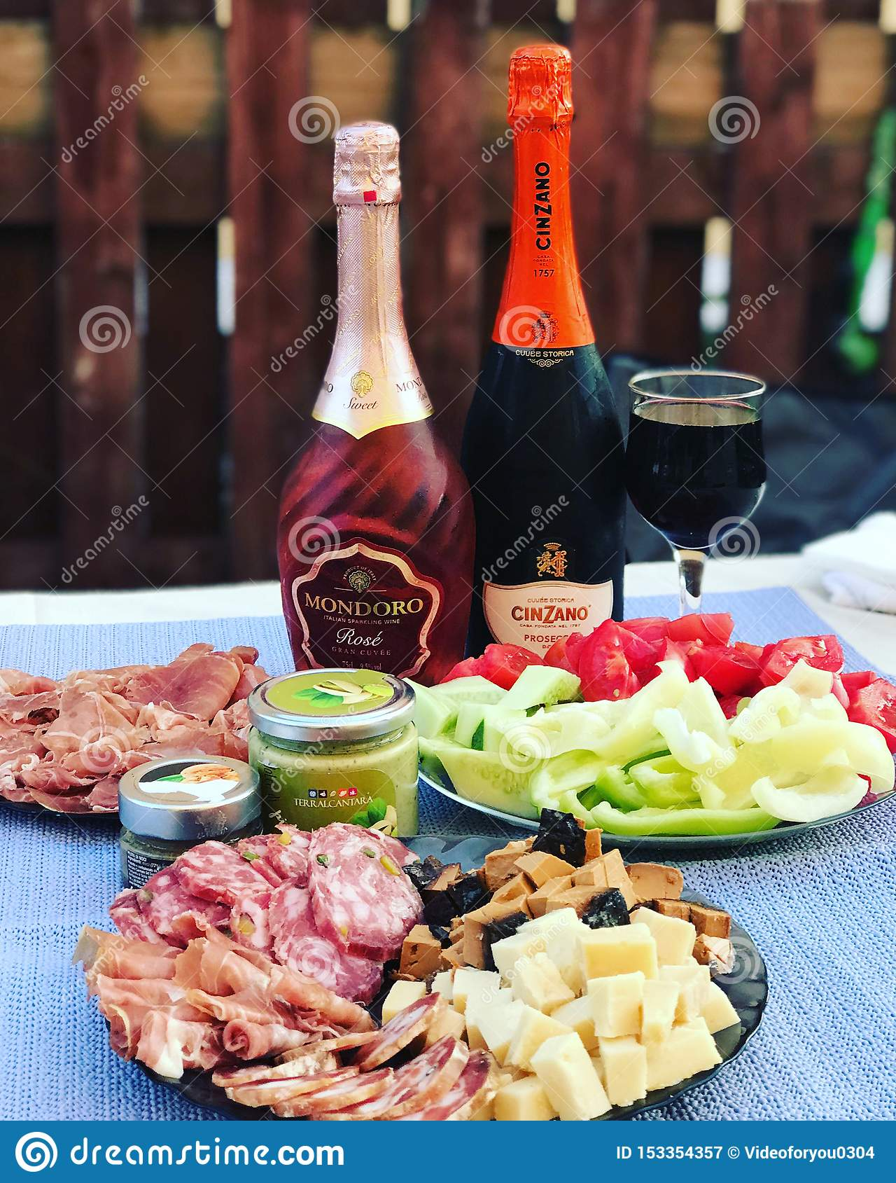 Russia, Tatarstan, July 27, 2018. A bottle of Cinzano proseco, a bottle of Mondoro rose, snacks: jamon, cheese, pesto, vegetables
