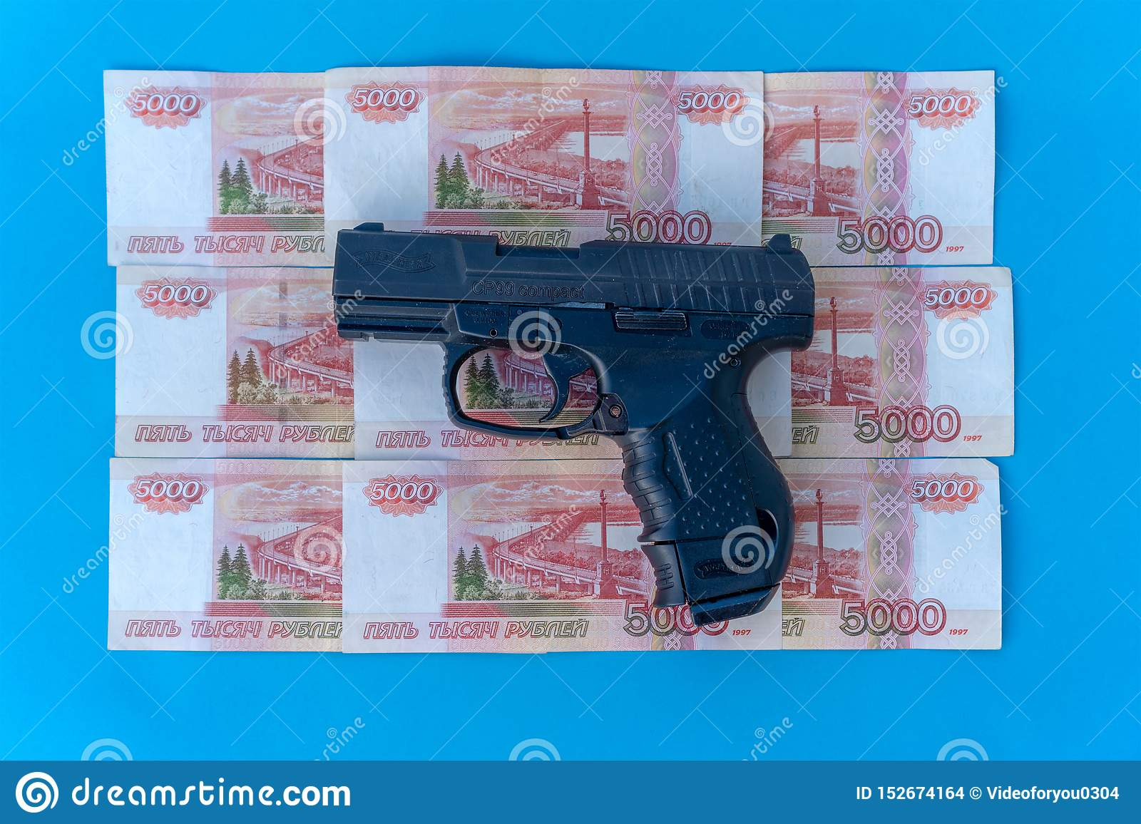 Close up image of pistol and rubles money. Walter and rubles on a blue background close-up