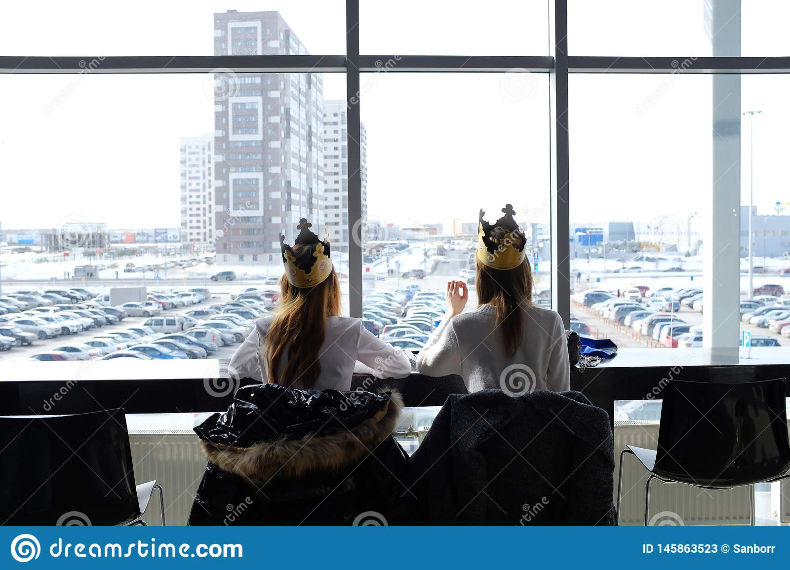 Russia, Tyumen, 30.03.2019. Teenage girls in crowns from Burger king for lunch at the Mall. Girls eat in the shopping center. Rear