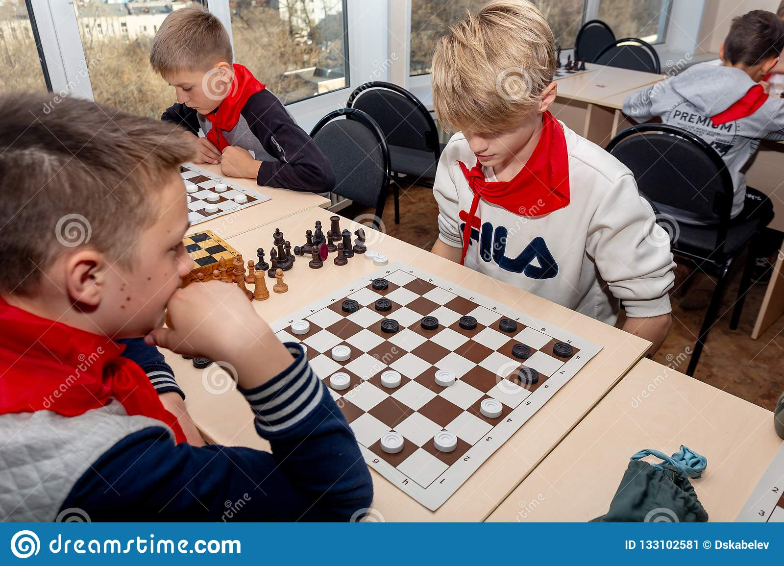 Russia, Vladivostok, 12/01/2018. Kids play chess during chess competition in chess club. Education, chess and mind games.