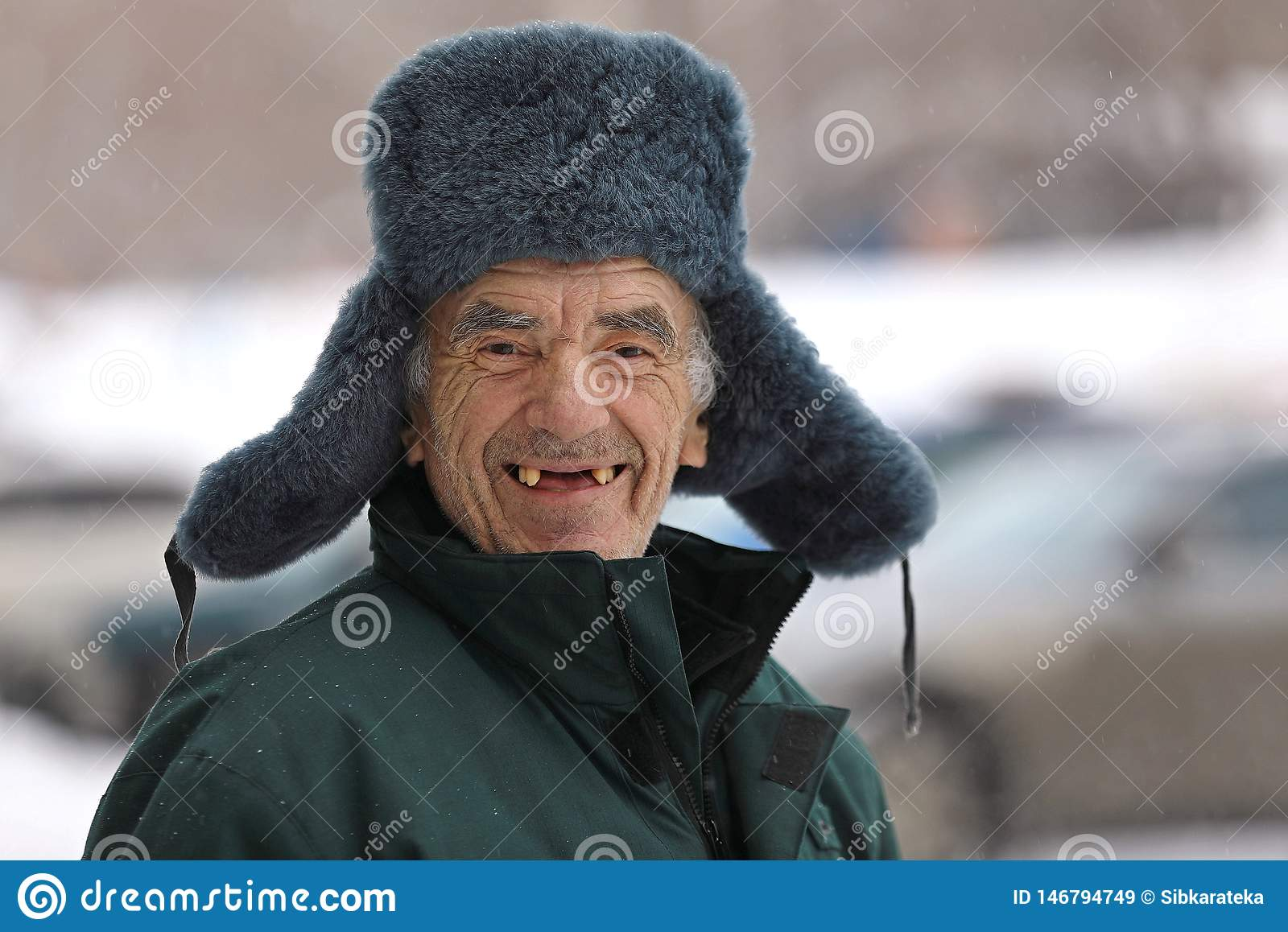 Russian old man in winter hat smiles