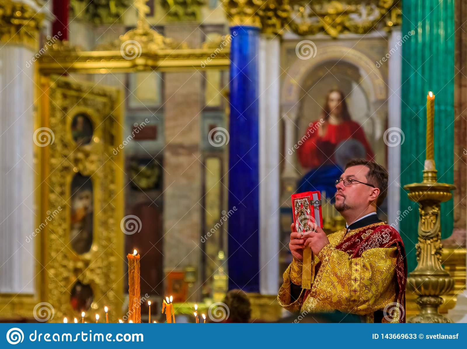 Russian Orthodox priest in traditional clothing serving in the Saint Isaac`s Russian Orthodox Cathedral in Saint Petersburg Russi