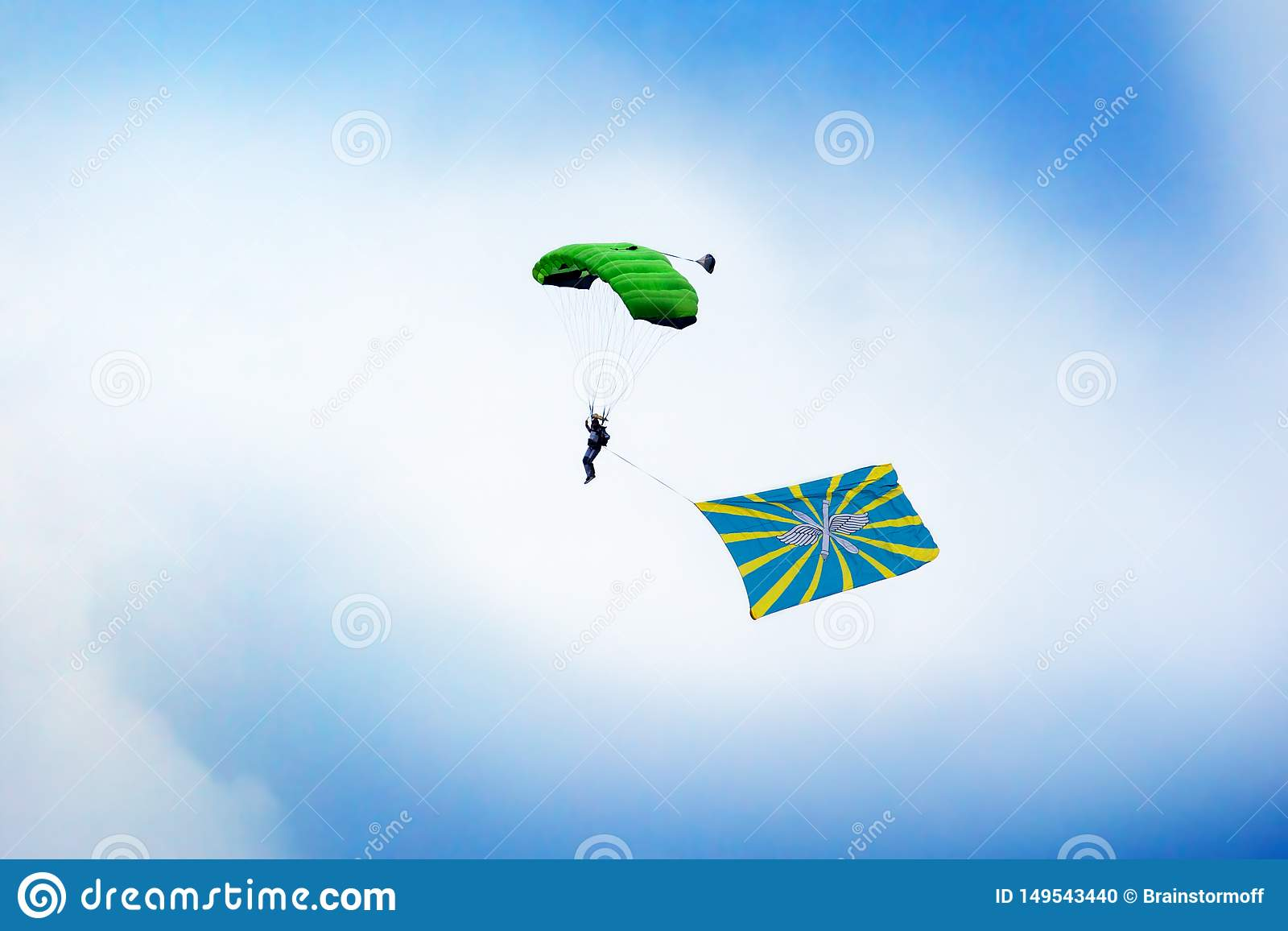 Russian paratrooper jumps with a parachute with Flag of Russian Air Force on clear blue sky and white clouds background