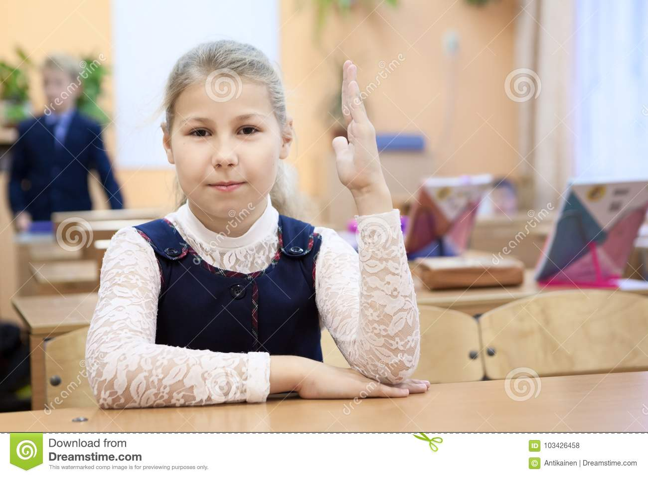russian schoolgirl Russian schoolgirl in uniform sitting at the desk in class room and rising  hand up. Russia