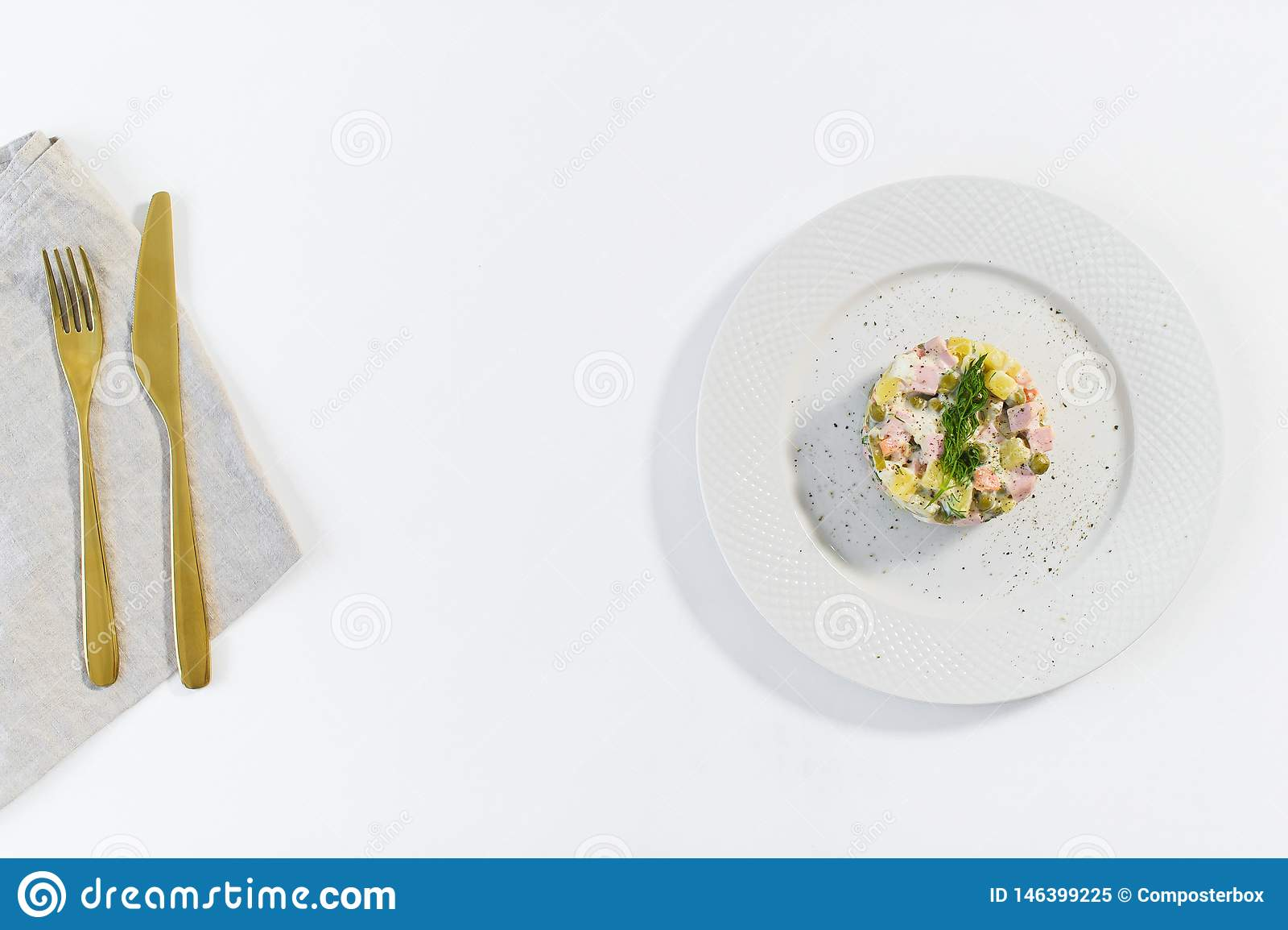 Russische salade op een witte plaat met een Gouden mes en vork op een witte achtergrond