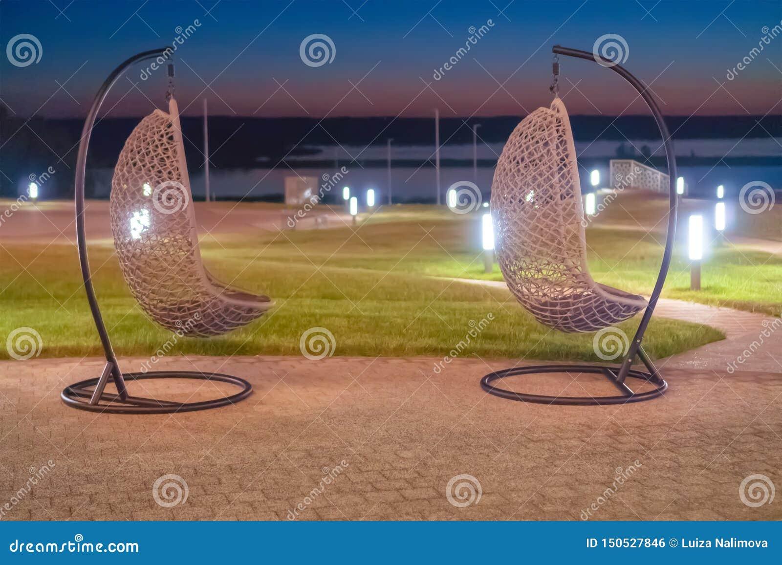 Russland, Bolgar - 8. Juni 2019 Kol Gali Resort Spa: Zwei hängende geflochtene Stühle des Rattans gegen das Meer