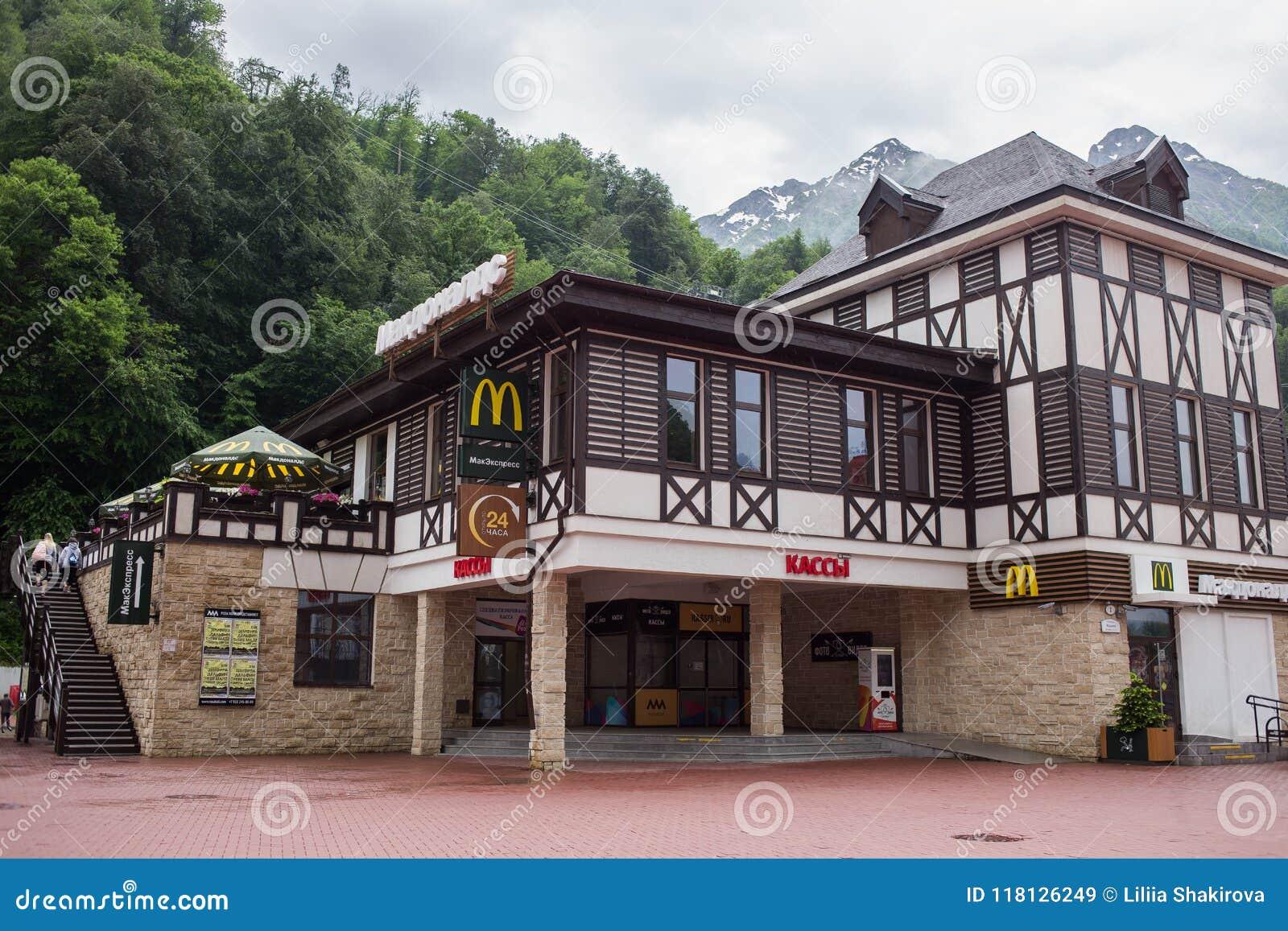 RUSSLAND, SOCHI - 25. MAI 2018: Redaktionelles Foto von McDonald-` s in Krasnaya Polyana, im Erholungsort gegen Berge