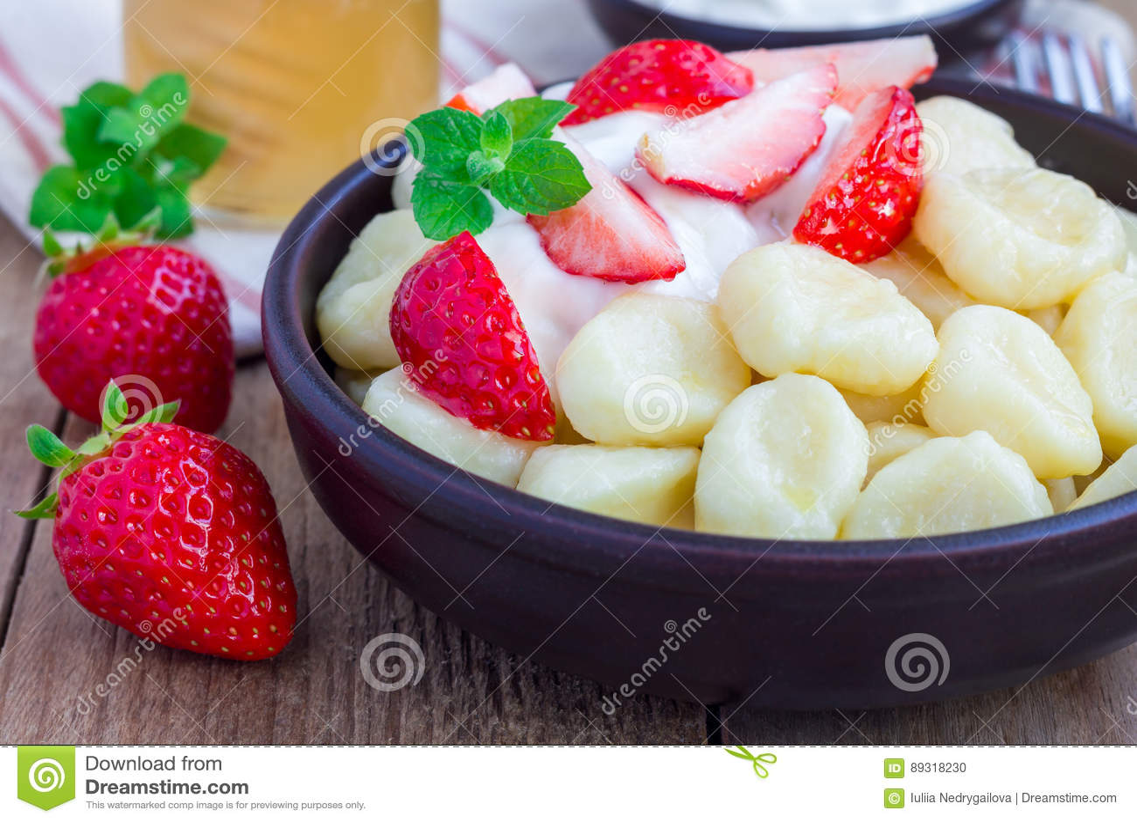Russo tradicional, requeijão ucraniano & x22; lazy& x22; as bolinhas de massa serviram com iogurte, mel e morango