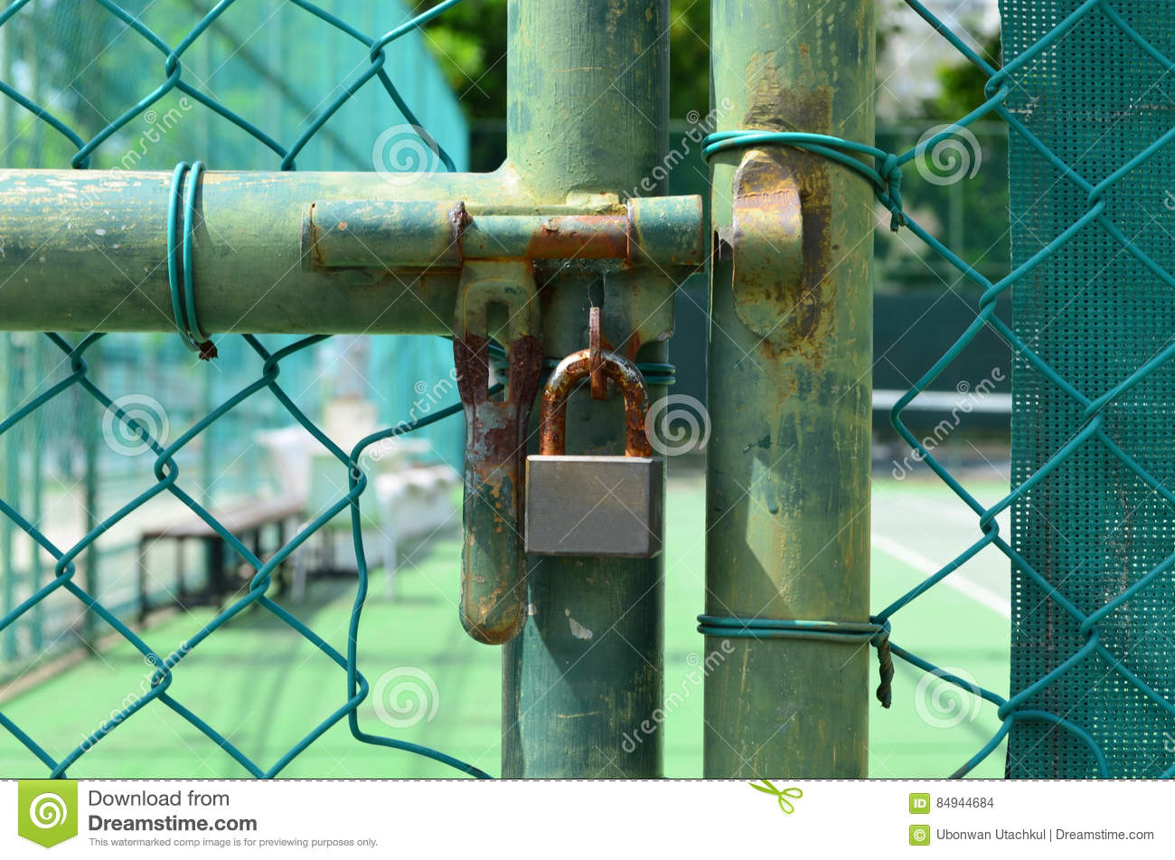 Rust lock at old green wire mesh fence in front of tennis court