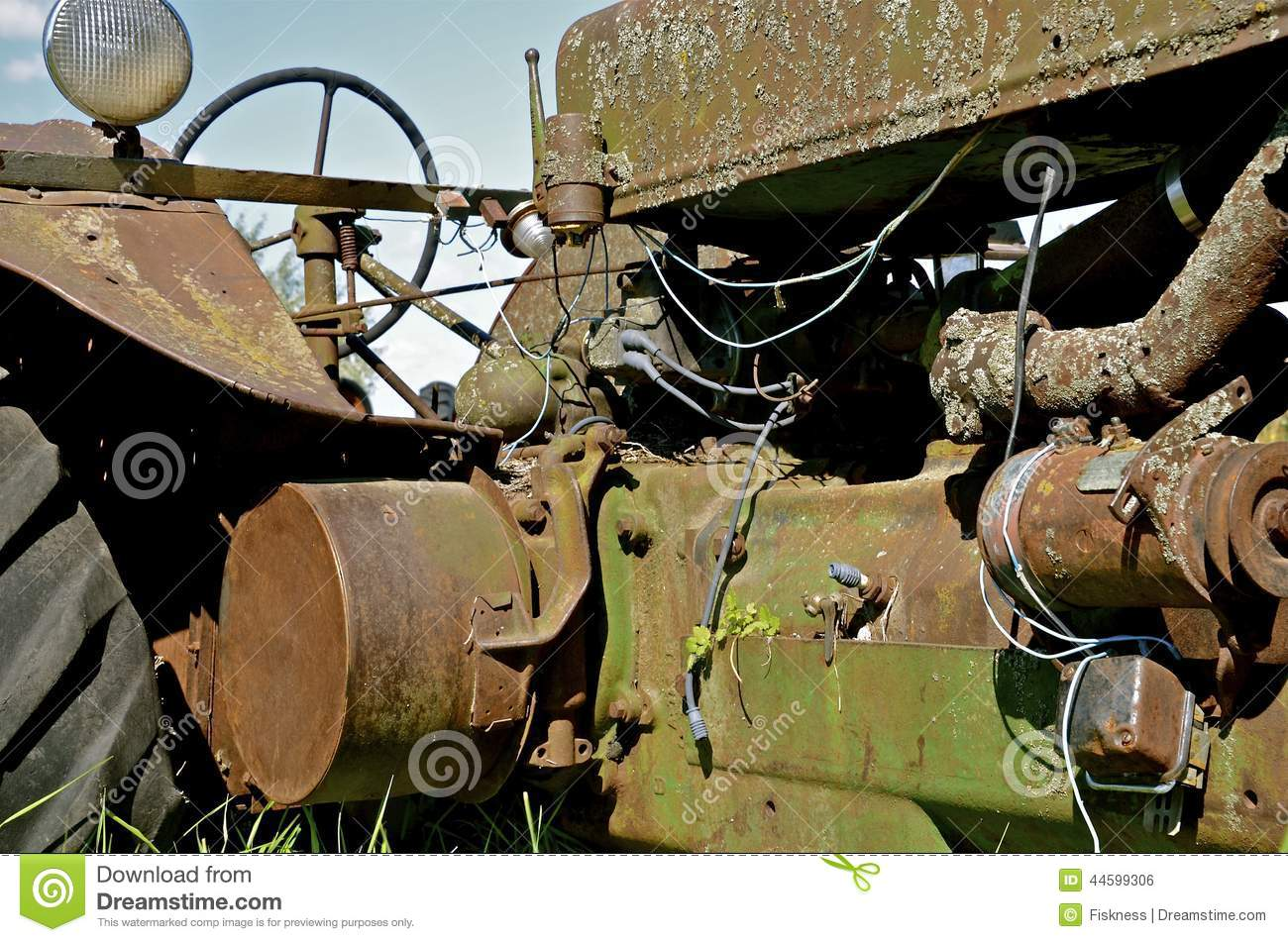 a rusty old tractor has cords and electrical wiring hang in from the hood  cover