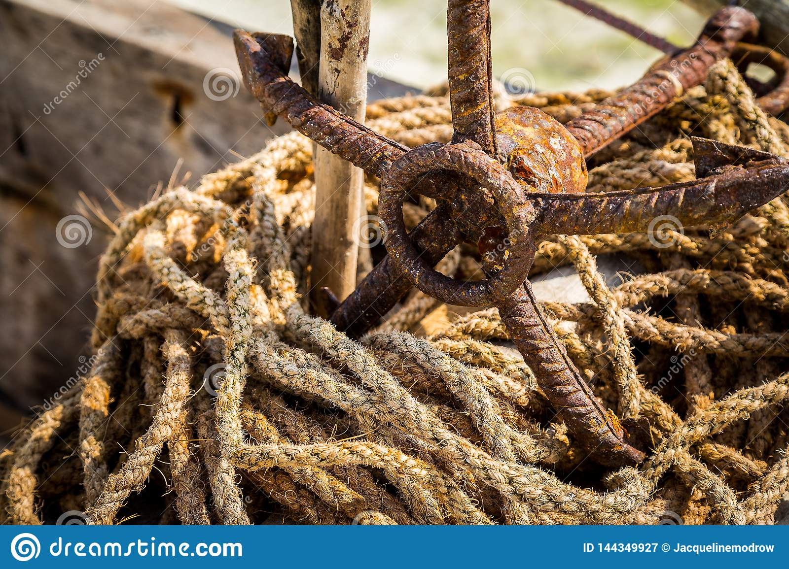 Rusted anchor with worn ropes on beach in Zanzibar