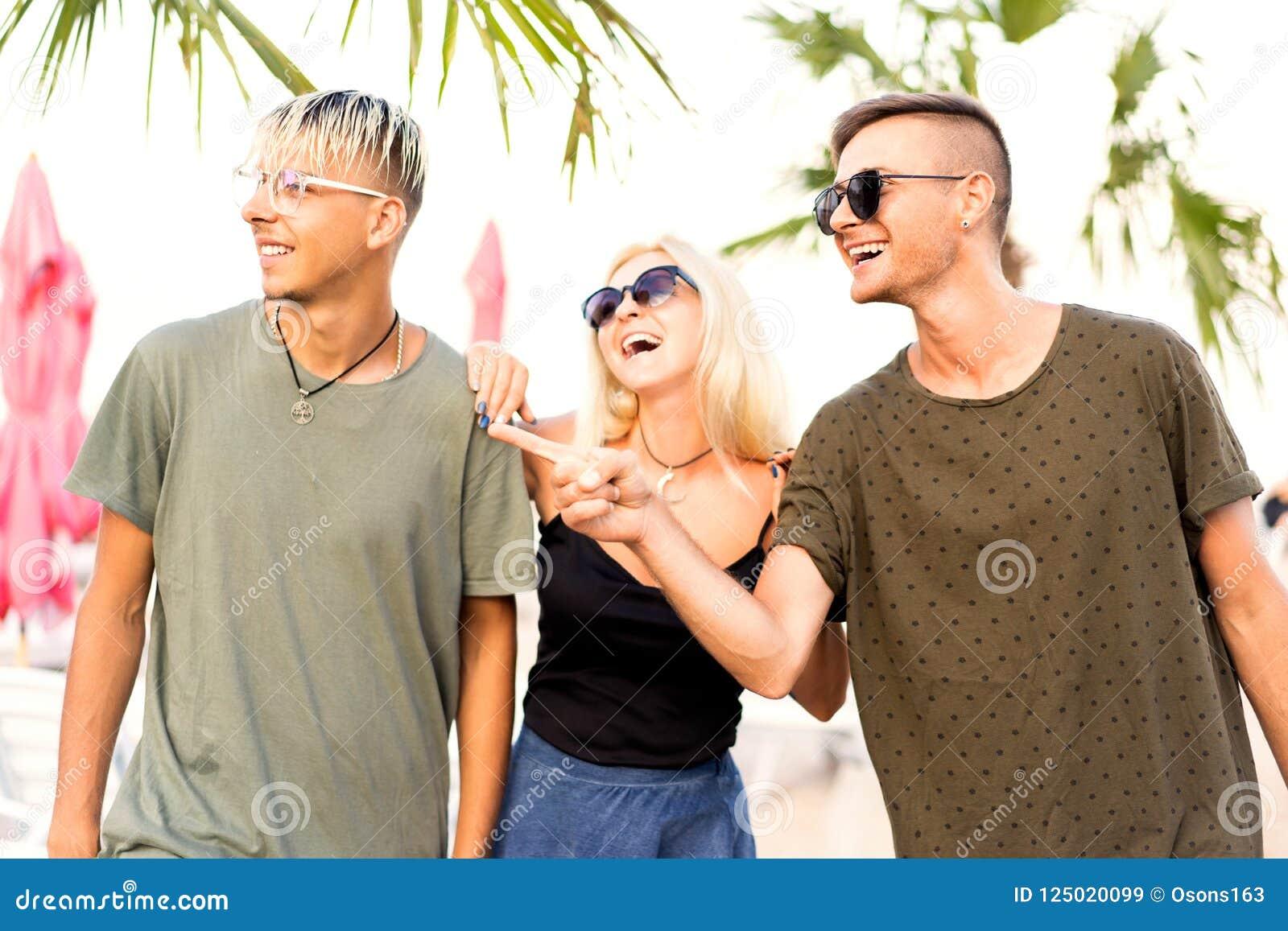 Rust van het drie vrienden de vrolijke bedrijf op een tropisch strand en drin