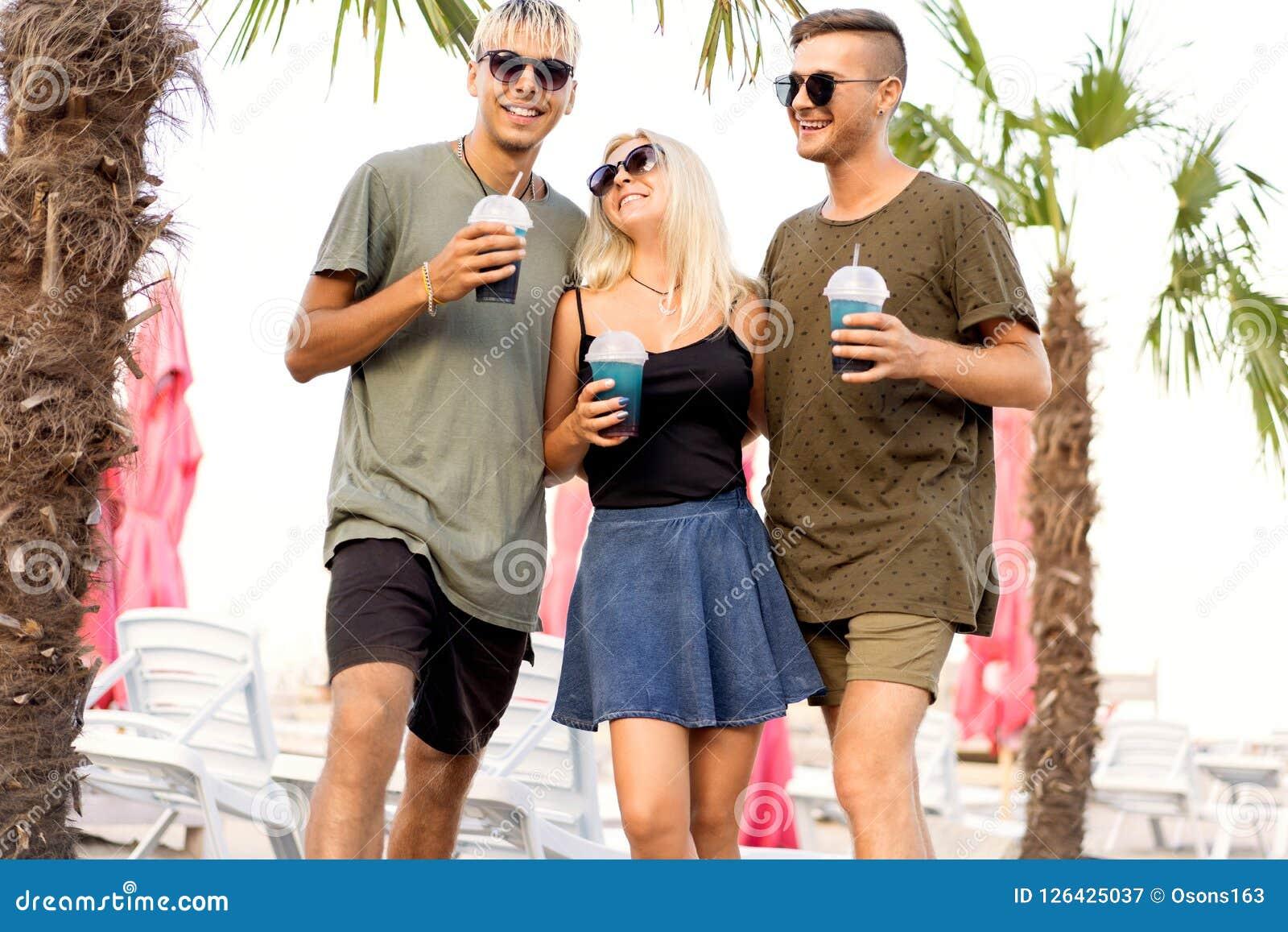 Rust van het drie vrienden drinkt de vrolijke bedrijf op een tropisch strand en cocktails; zeer; tijdschriftconcept