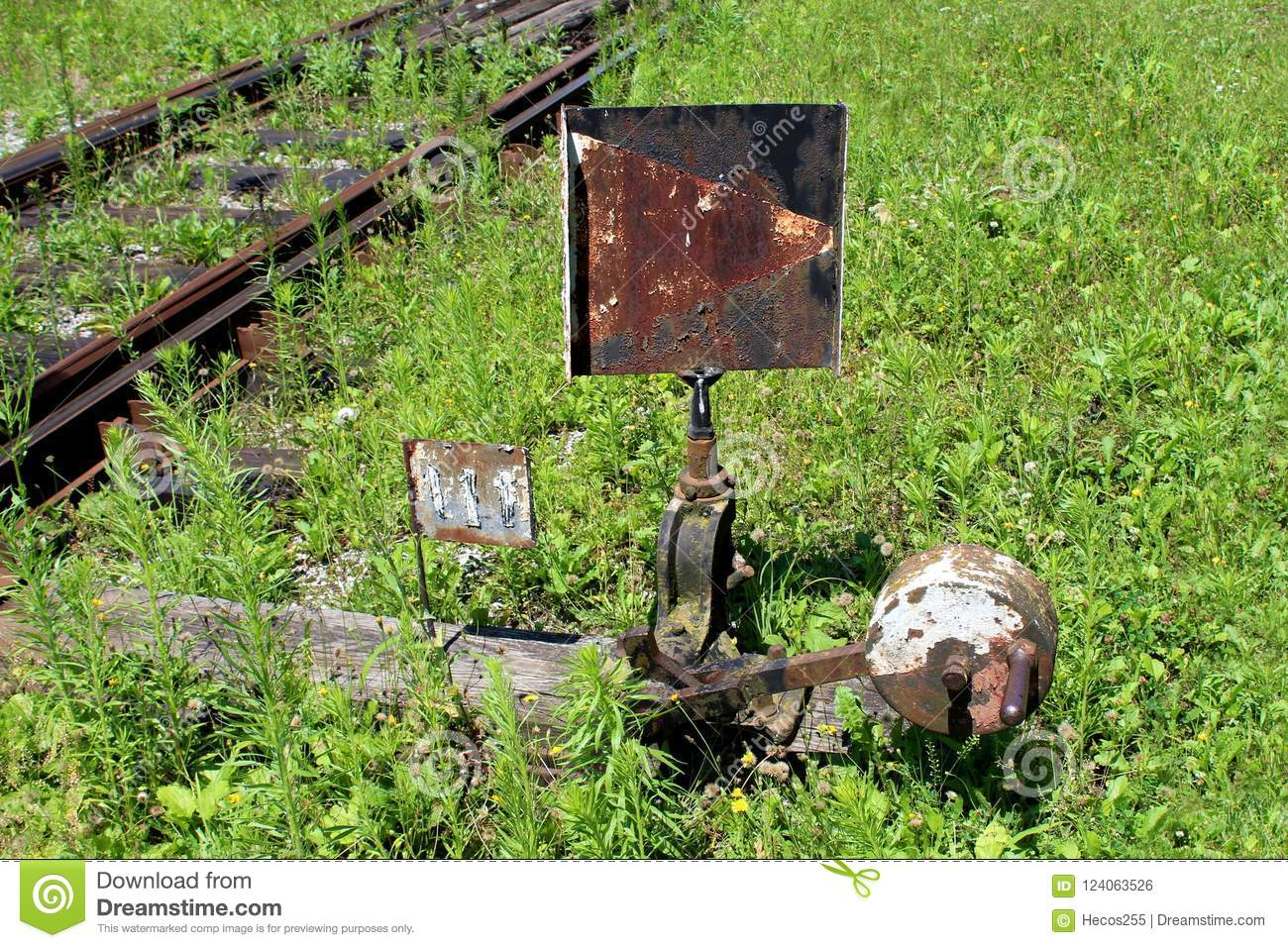 Rusted metal black and white railway switch mechanism with metal sign mounted on wooden board