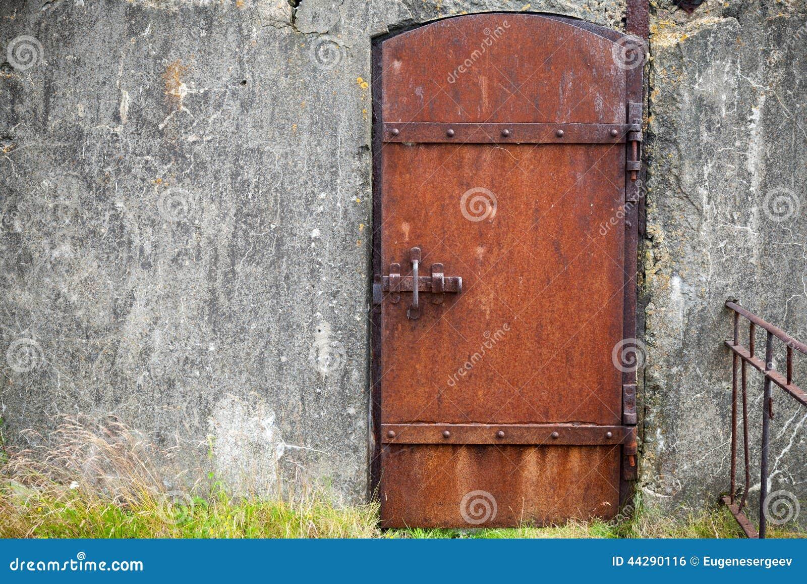 Rusty Metal Door rusted metal door in old wall, background texture stock photo