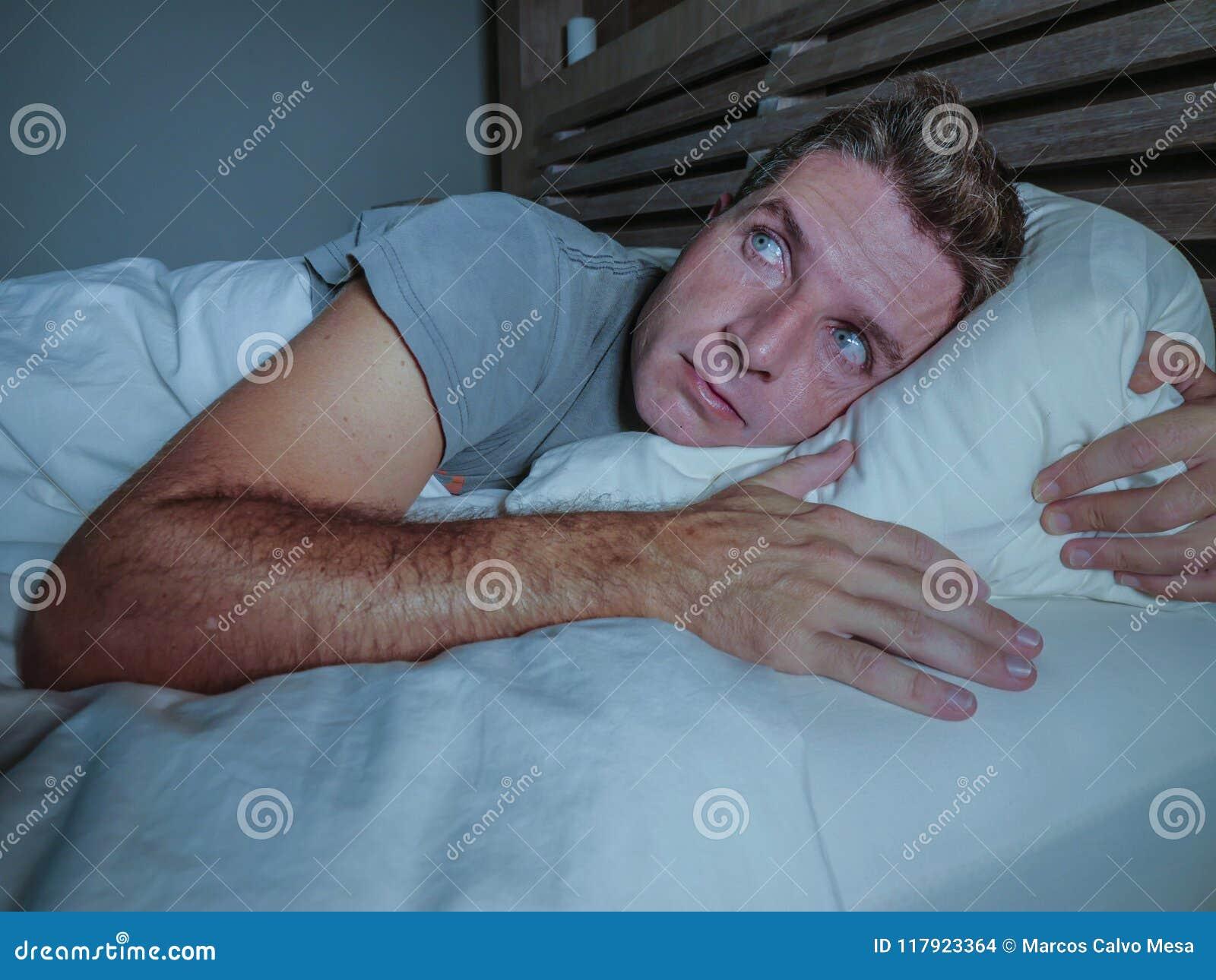 Rusteloze ongerust gemaakte jonge aantrekkelijke mens wakker bij nacht die op bed slapeloos met wijd geopende ogen liggen lijdend
