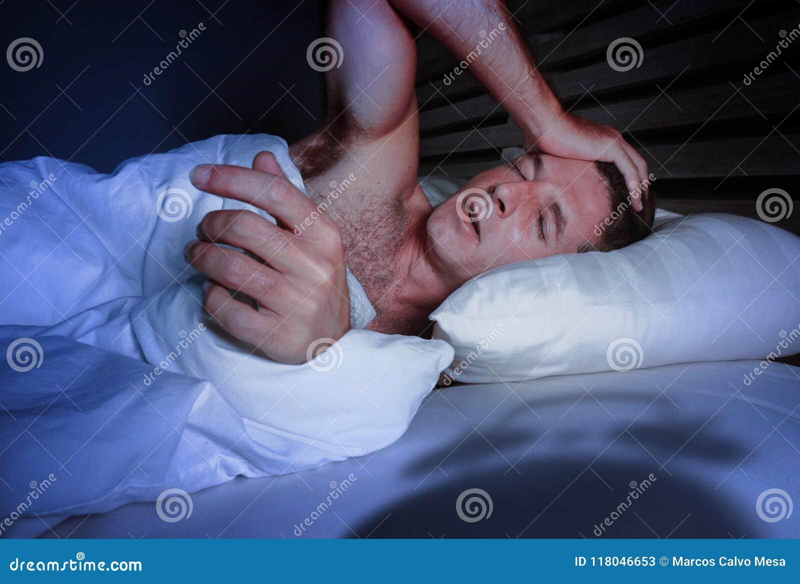 Rusteloze ongerust gemaakte jonge aantrekkelijke mens wakker bij nacht die op slaap dis liggen van de bed de slapeloze wanhopige
