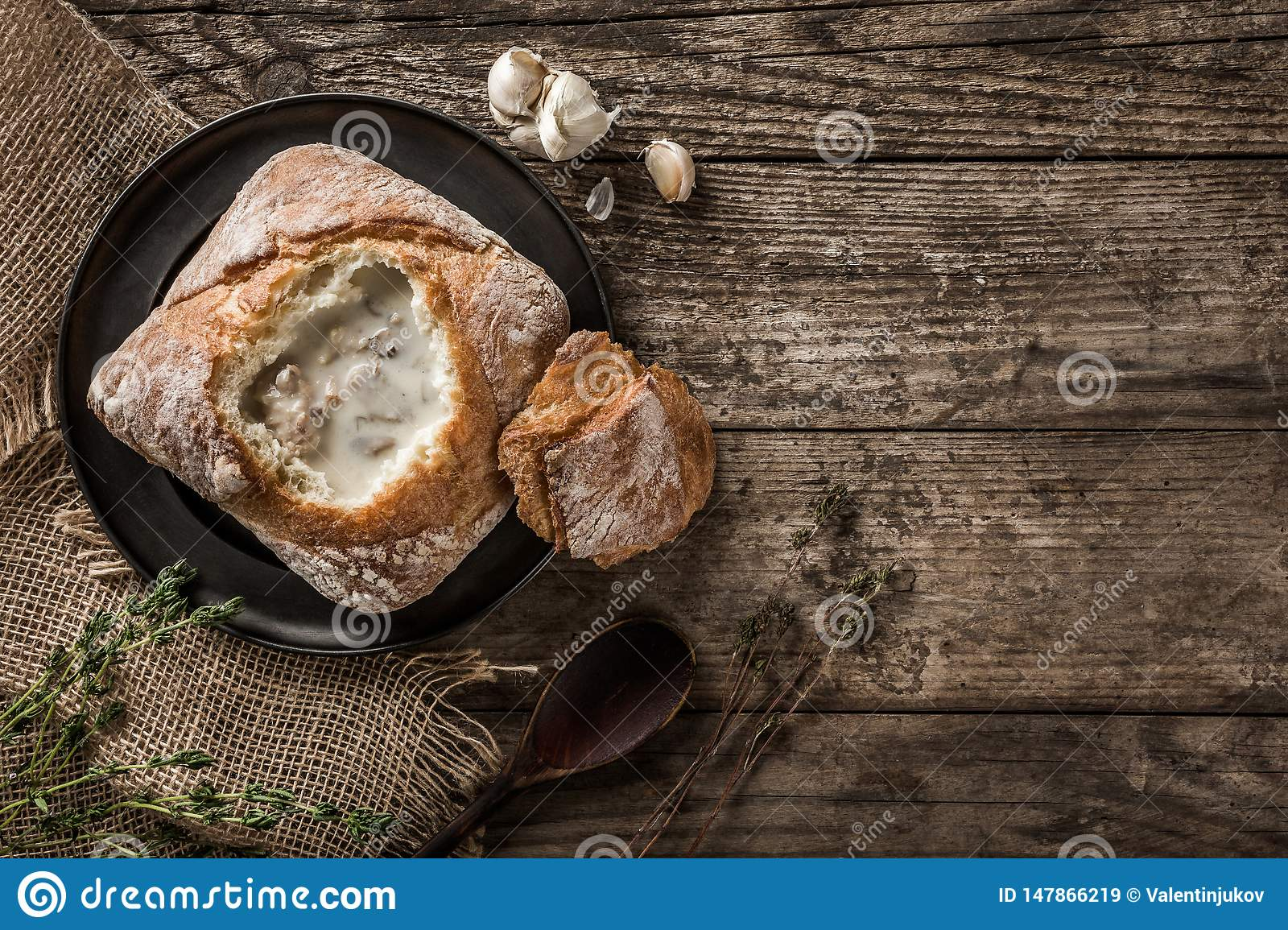 Rustic chicken soup with mushrooms in bread with spices on rustic wooden background. Healthy food concept, top view, flat lay,
