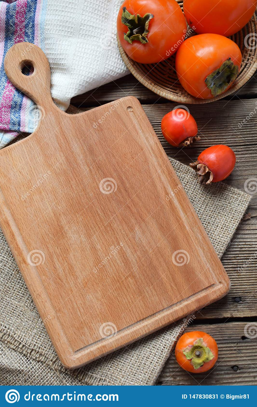 Rustic composition with different varieties of persimmons and wooden cutting board. Country style. Baking or cooking background.