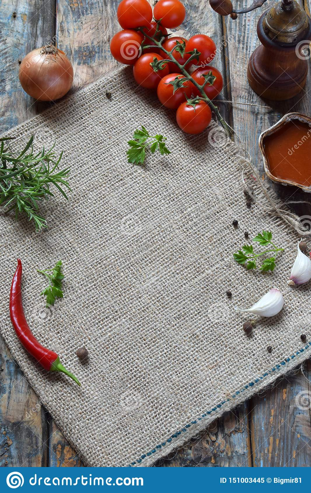 Rustic composition with pepper mill, tomato souce, fresh herbs, vegetables and spices. Country style. Baking or cooking background