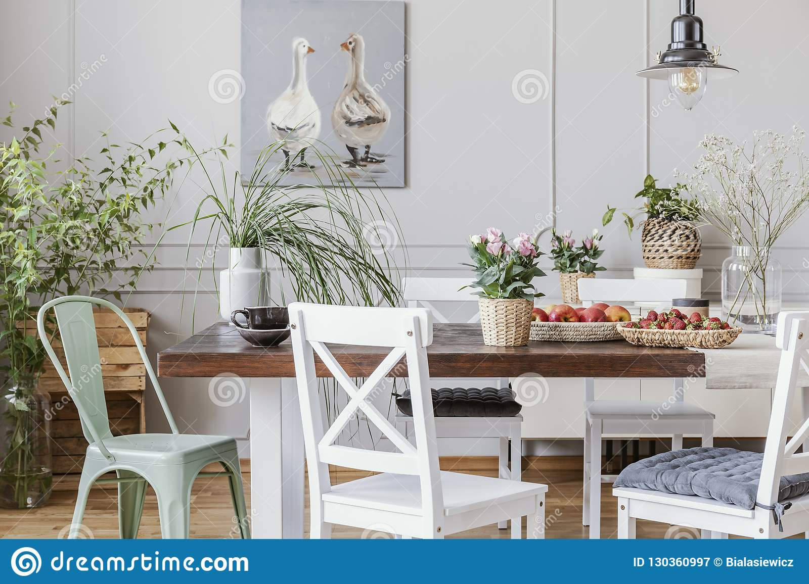 Rustic Dining Room With Long Table And White Chairs And Oil Painting