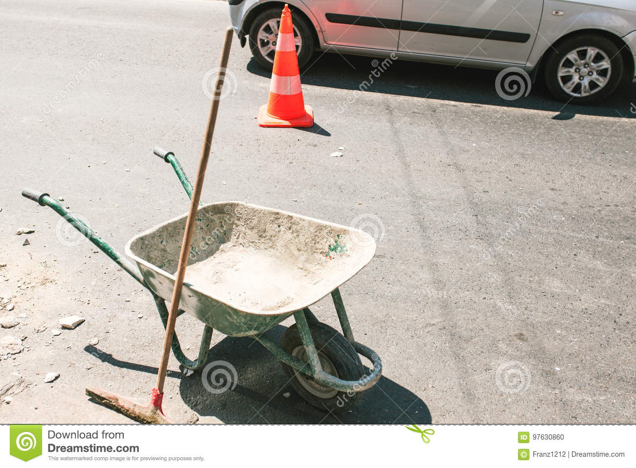 Rustic dirty construction wheelbarrow with push broom on the street, orange road construction cone in the background.