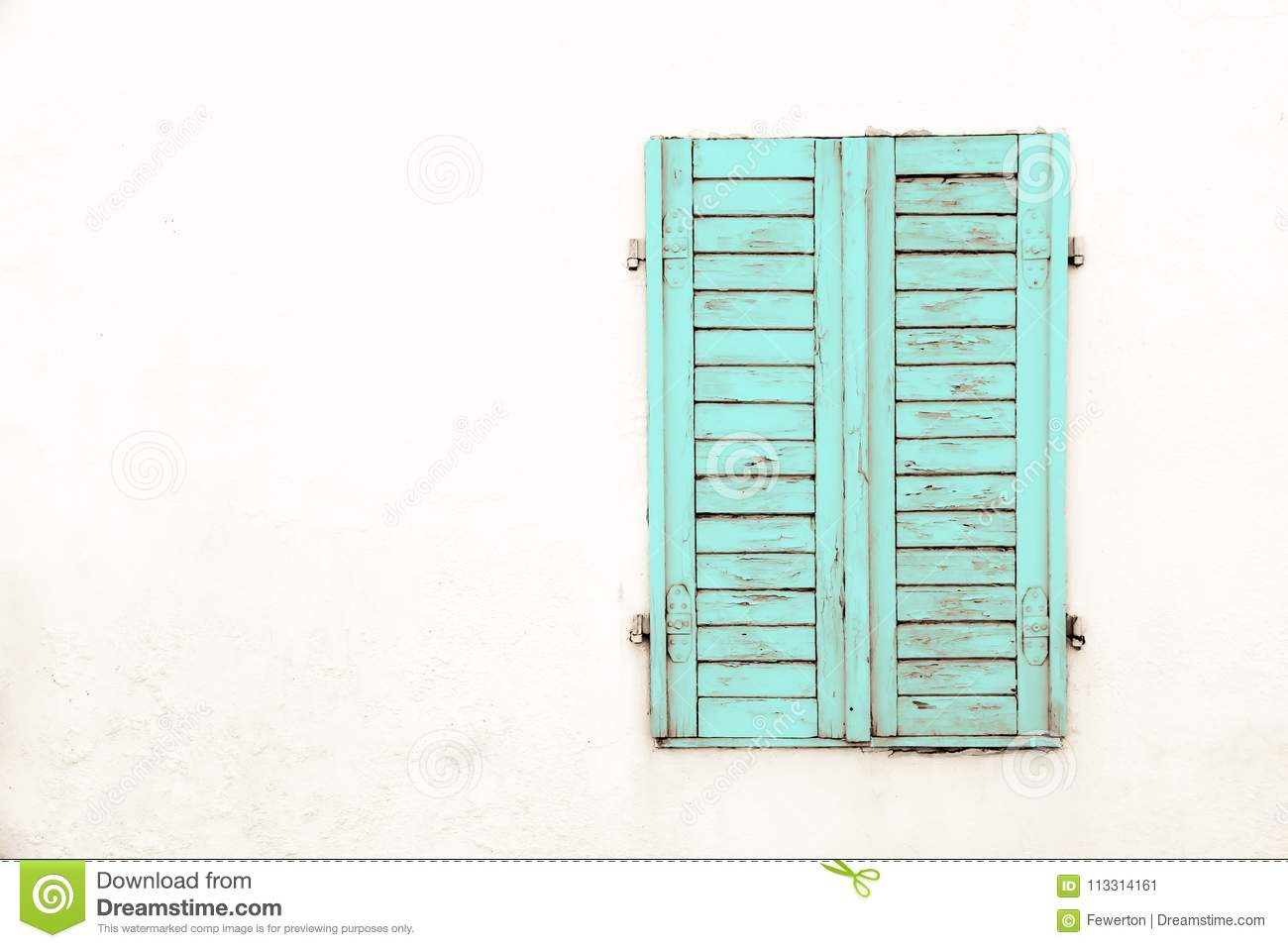 Rustic old grungy and weathered green cyan wooden closed window shutters with peeling paint