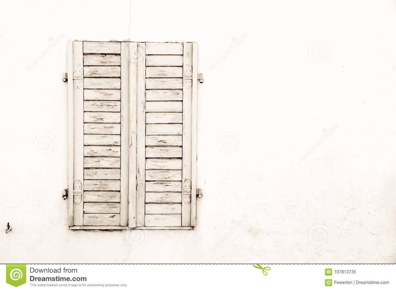 Rustic old grungy and weathered white grey wooden closed window shutters with peeling paint
