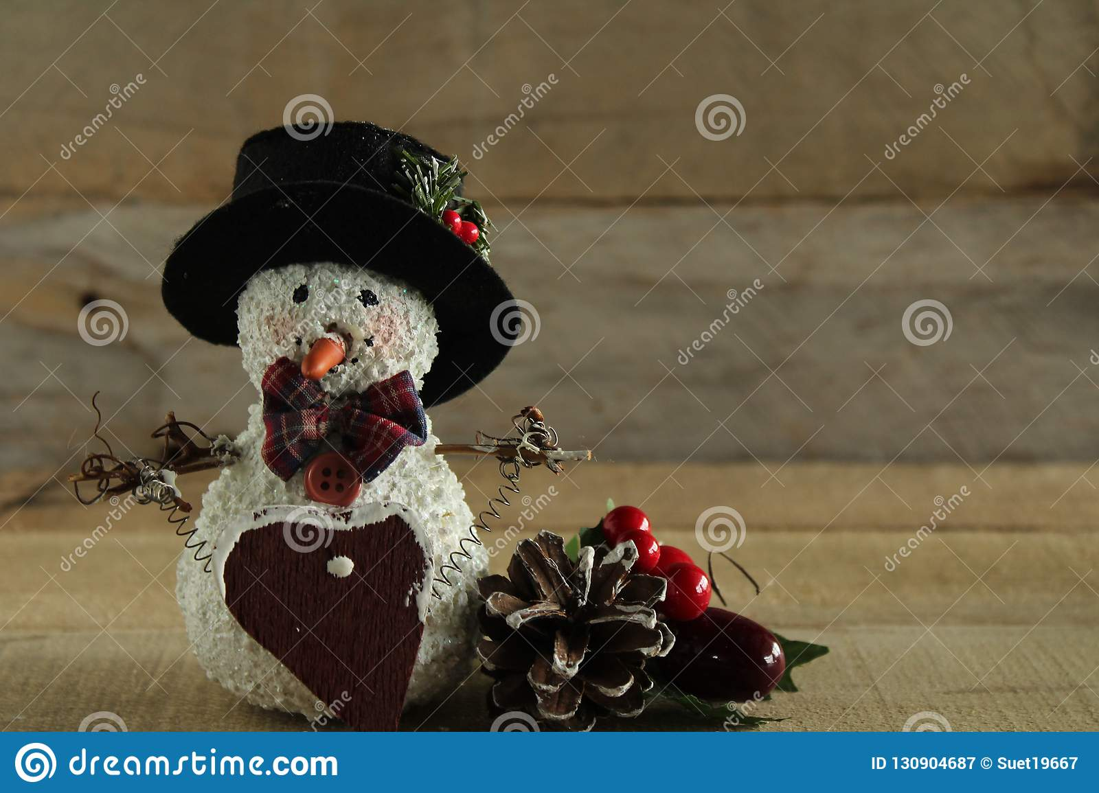 Primitive Snowman And Pine Cone On Wood Background Stock