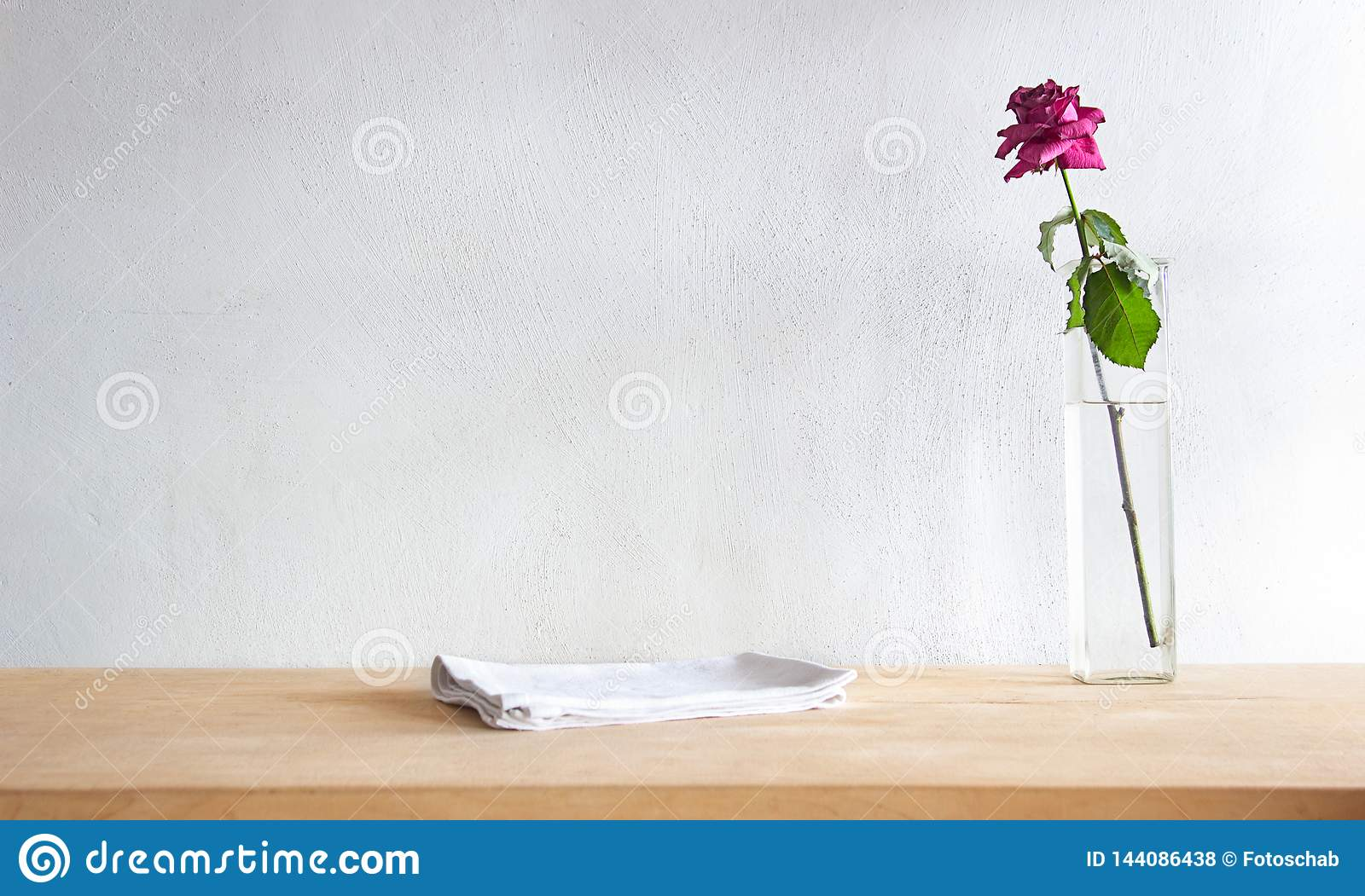 Rustic table with a white table linen and red, dried rose against grunge cement wall.
