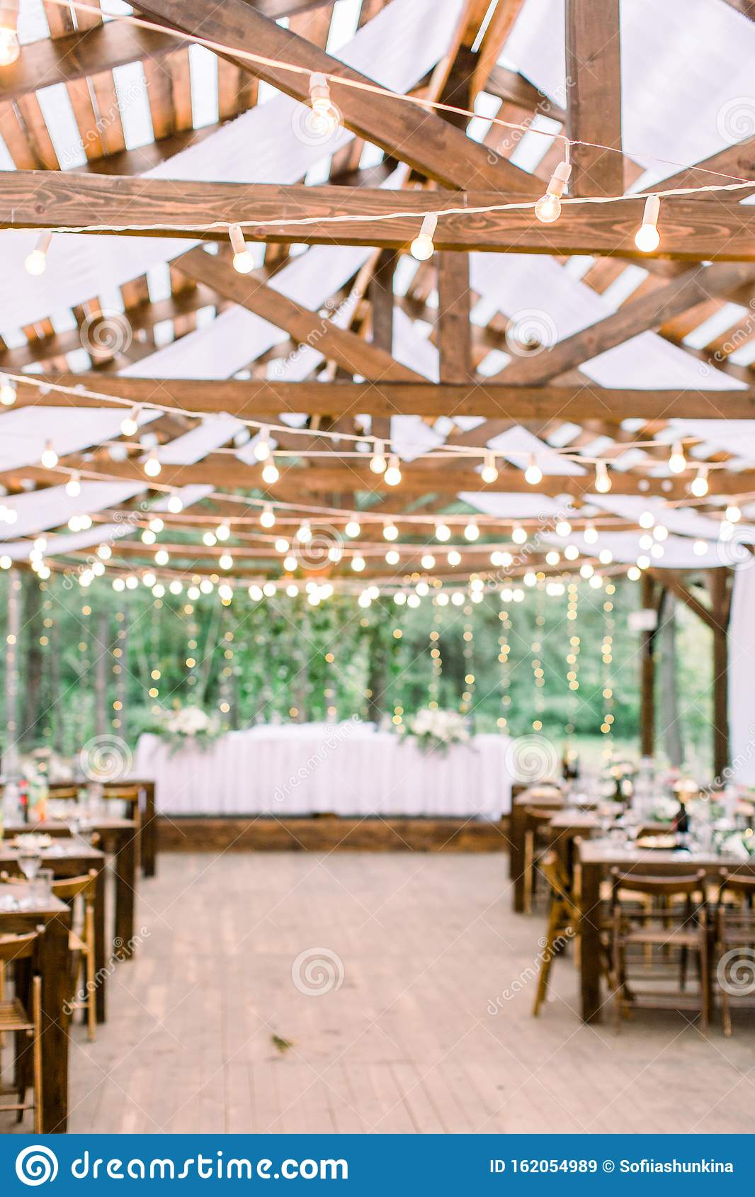 Rustic Tent Restaurant With Wedding Or Dinner Table And Floral Decorations And Light Bulbs On A Background Of Green Stock Image Image Of Decoration Event 162054989