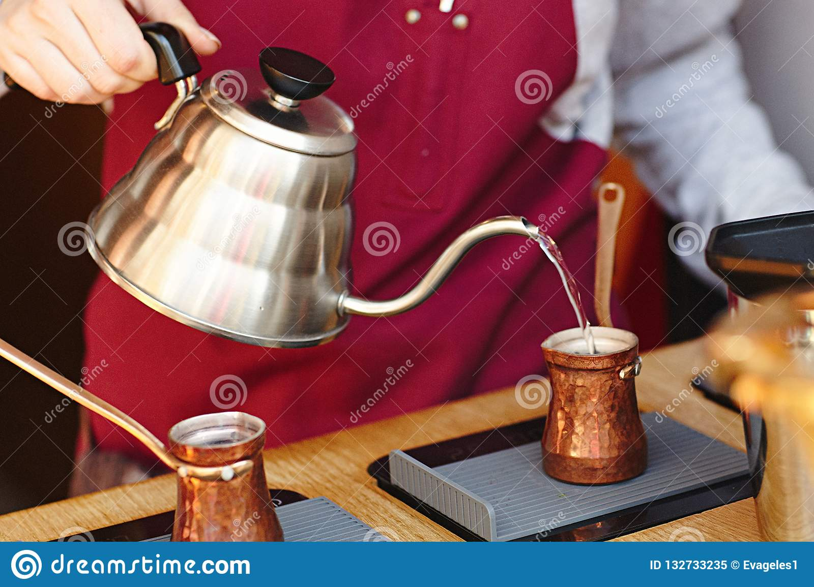 Rustic Turkish cezve, coffeepot, ibrik with boiled coffee beans, water, spices, cinnamon, salt on electric stove and wooden table.