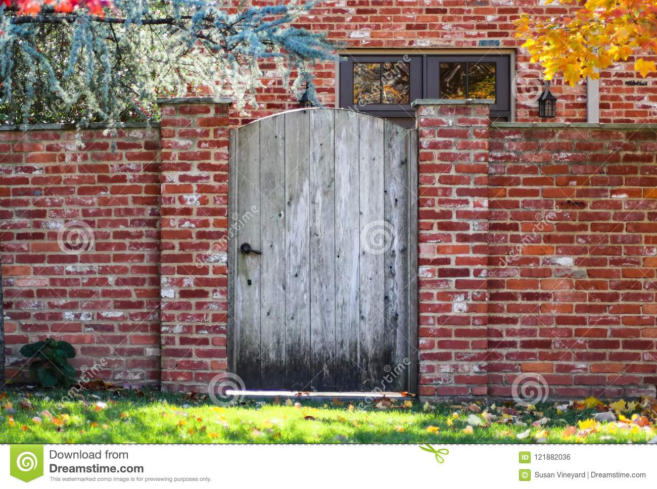 Rustic Wooden Arched Garden Fence In Brick Wall In Autumn With