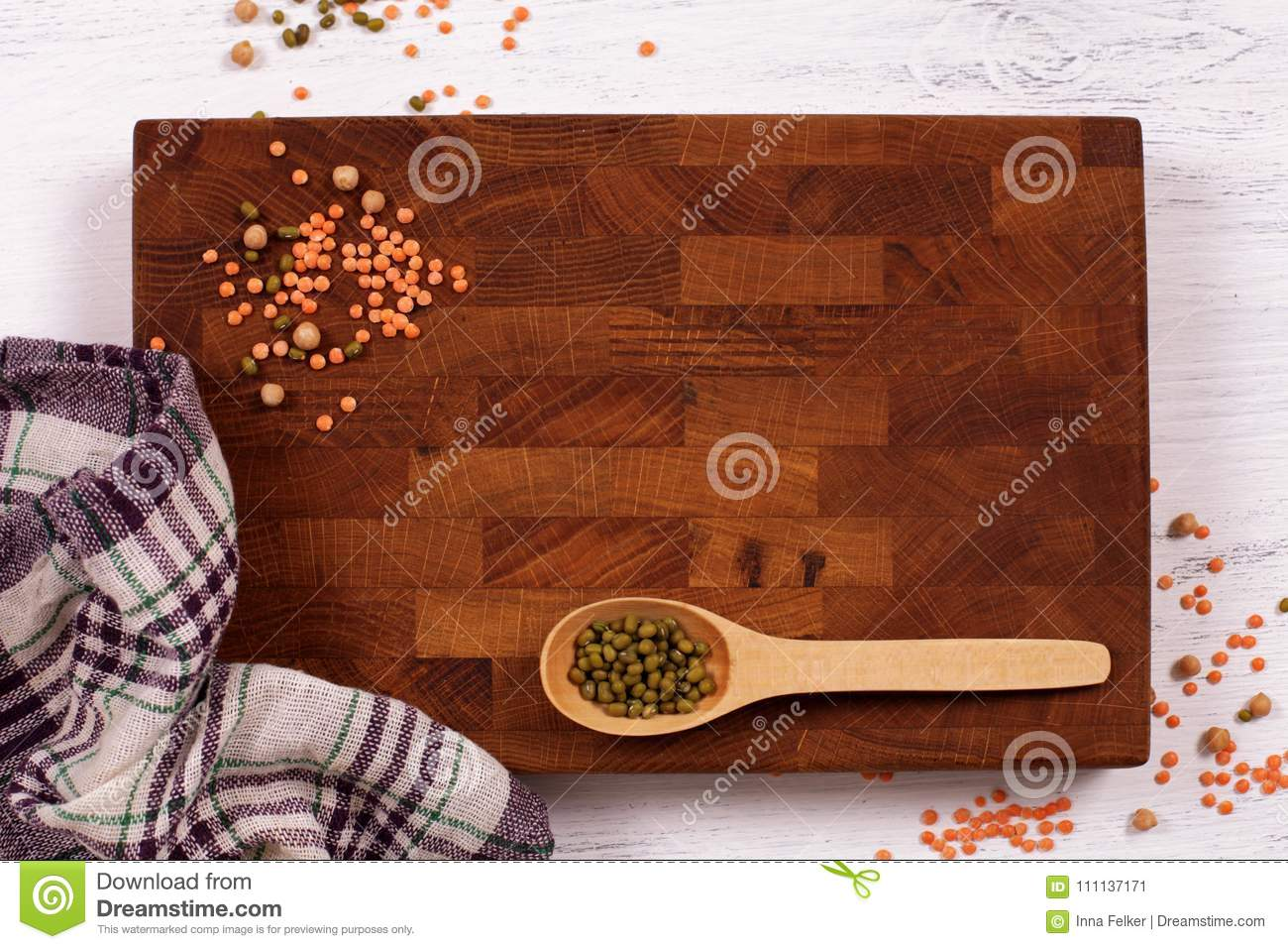 Rustic wooden board, checkered napkin and lentils seeds with cop