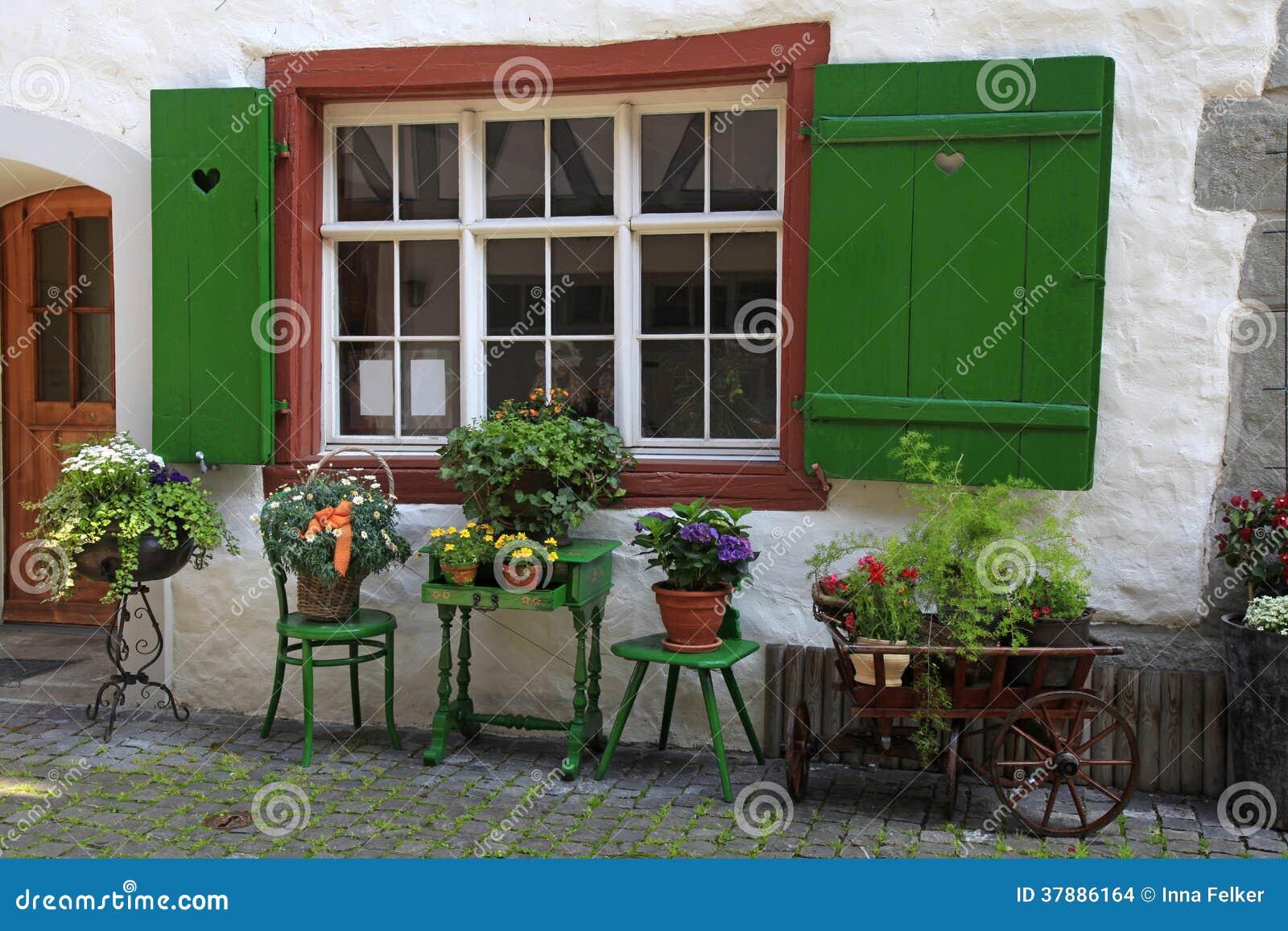 Rustiek venster met groene blinden en bloempotten